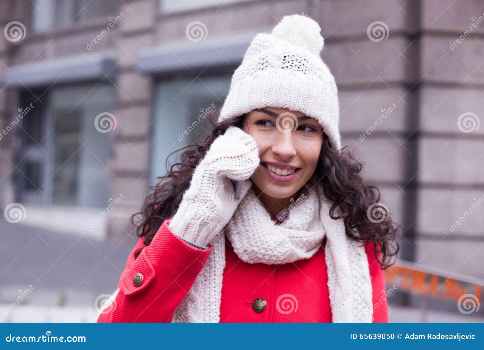 Femme dans le chapeau rouge de manteau et de laine et gants avec le smartphone en Han