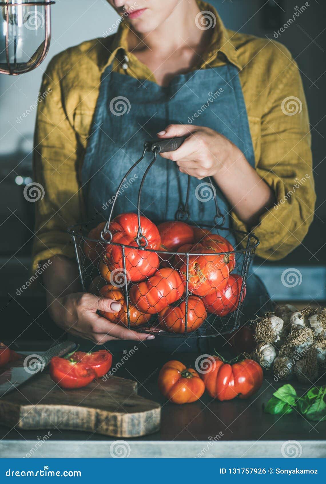 Femme dans le panier de participation de tablier avec des tomates d héritage
