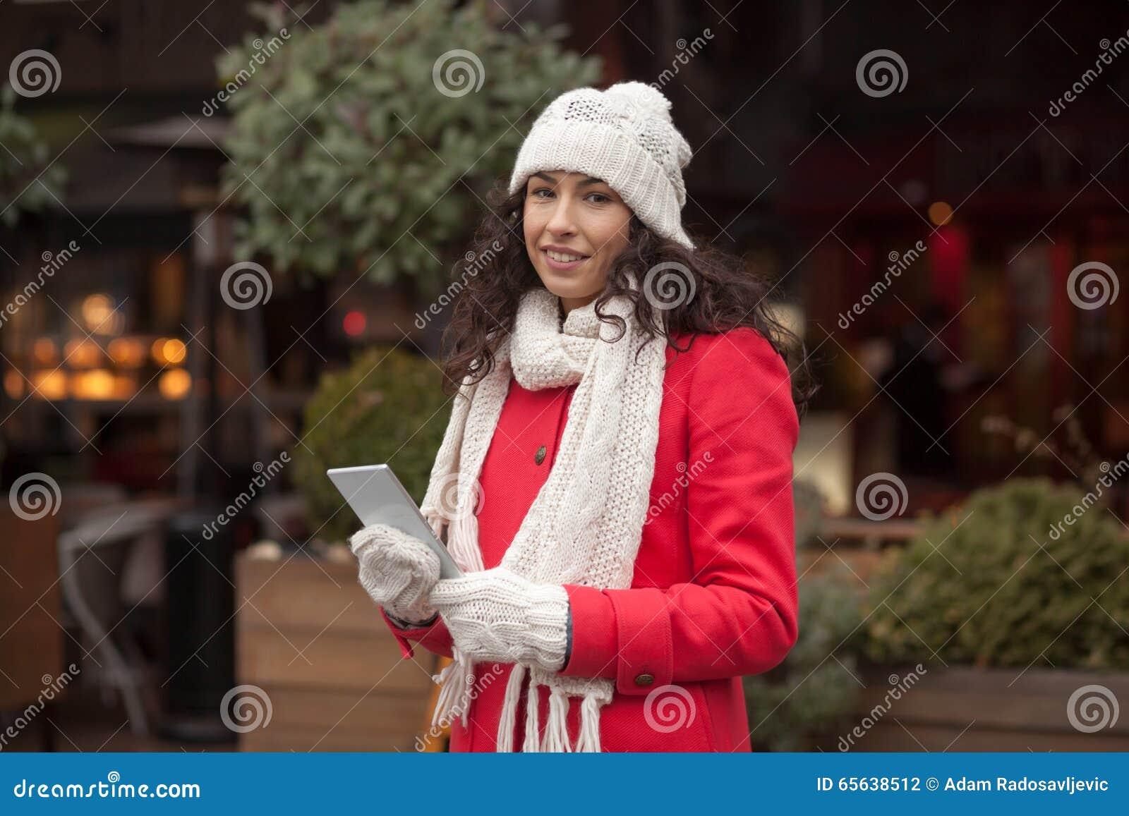 Femme dans le Smart-téléphone de prise de gants de laine