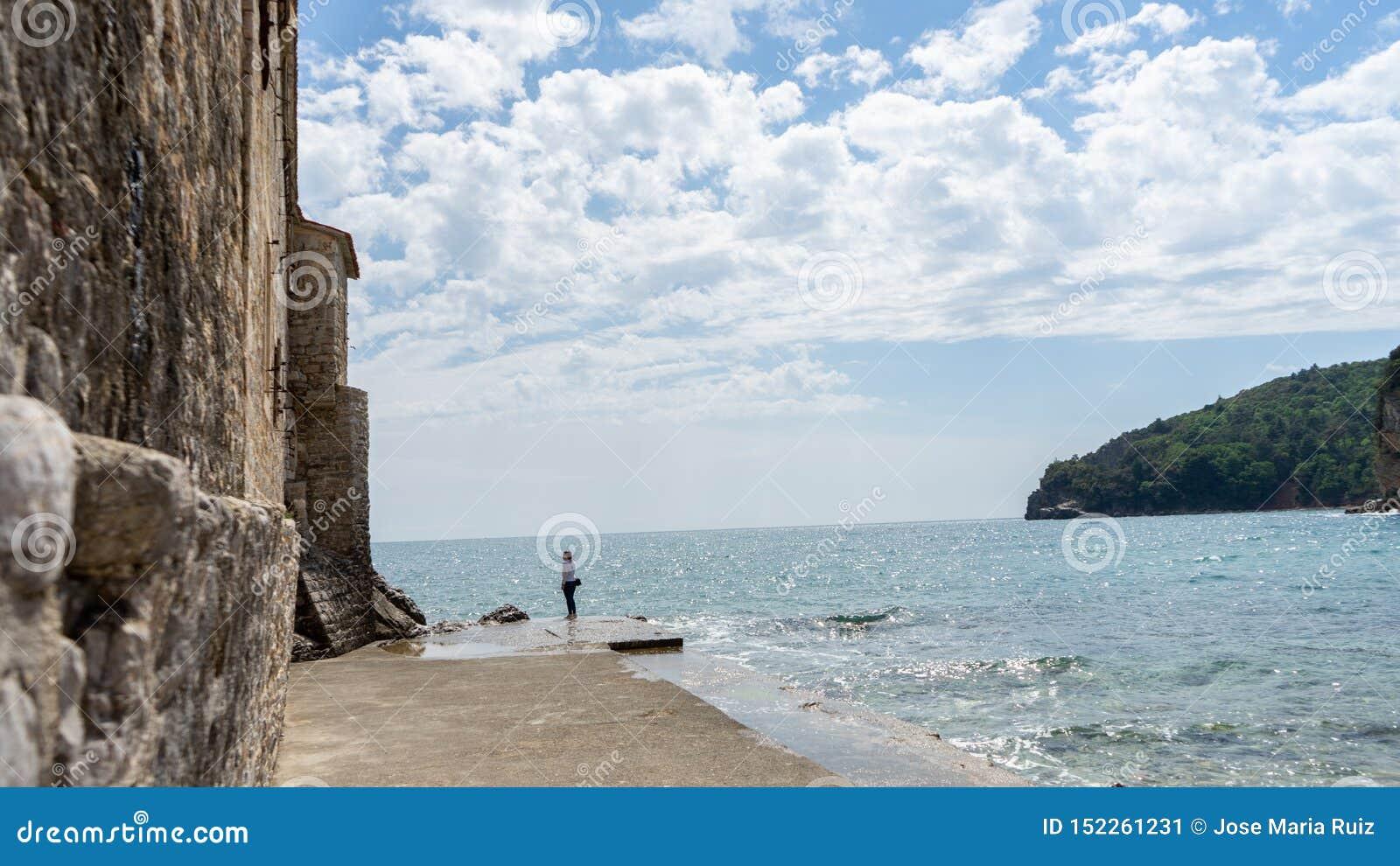 Femme dans un port en pierre dans une vieille ville de la Mer Adriatique L eau dans un pilier de roche et un mur médiéval en deho