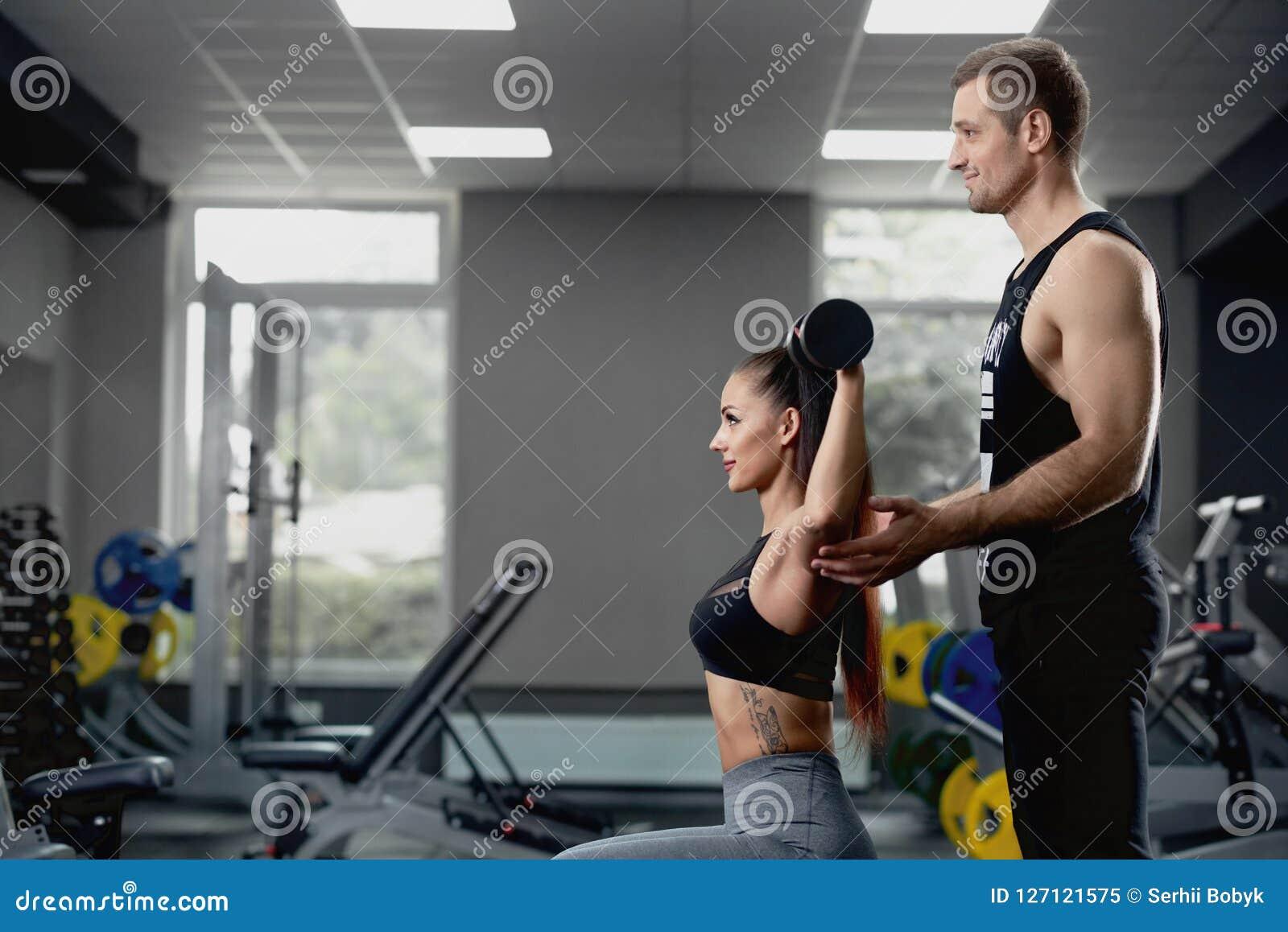 Femme de aide d entraîneur personnel masculin travaillant avec les haltères lourdes au gymnase