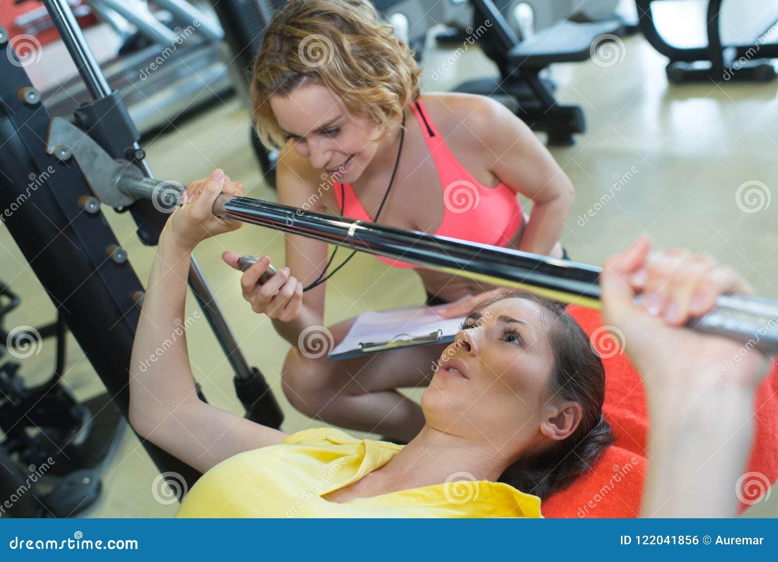 Femme de aide d entraîneur personnel pour la presse-formation correcte de banc