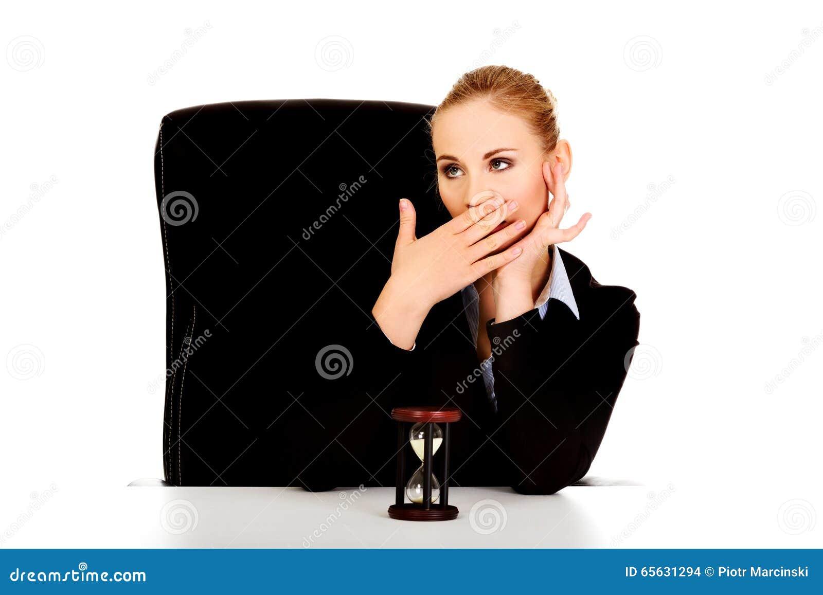 Femme de baîllement d affaires avec le sablier sur le bureau