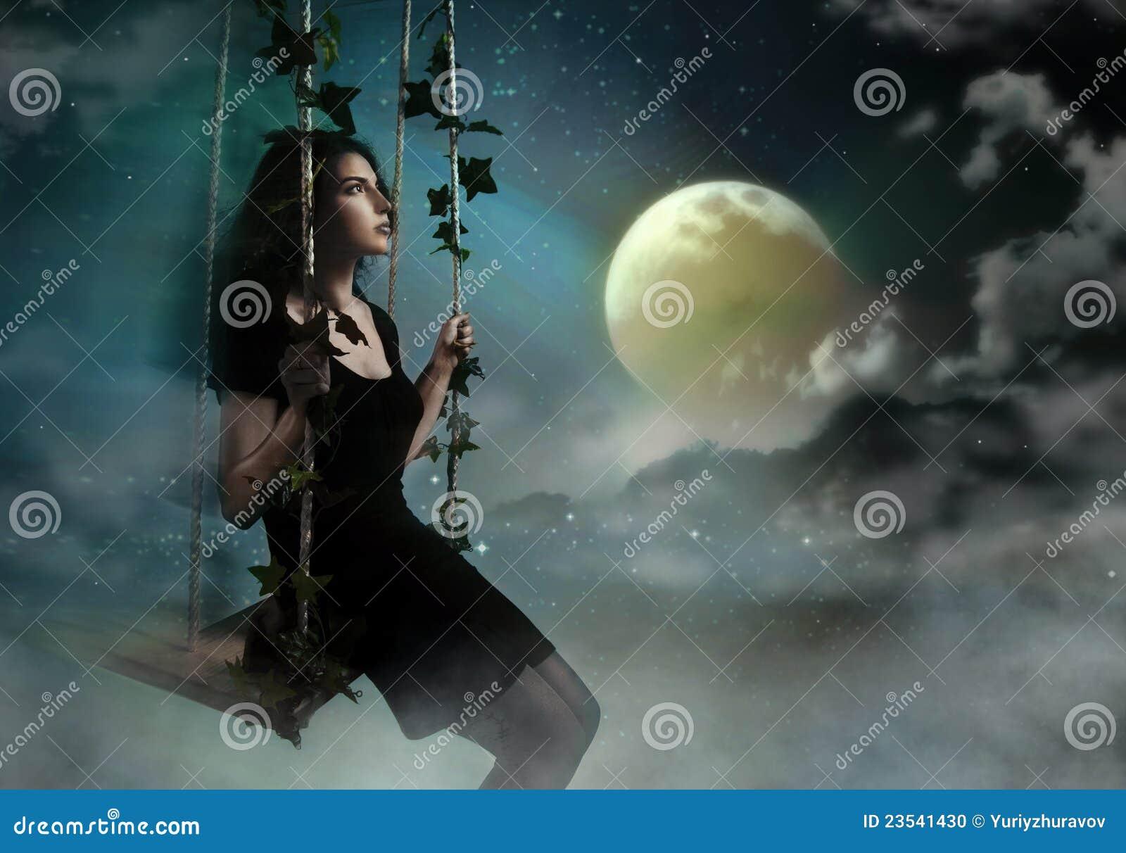 Femme de beauté balançant dans le ciel de nuit