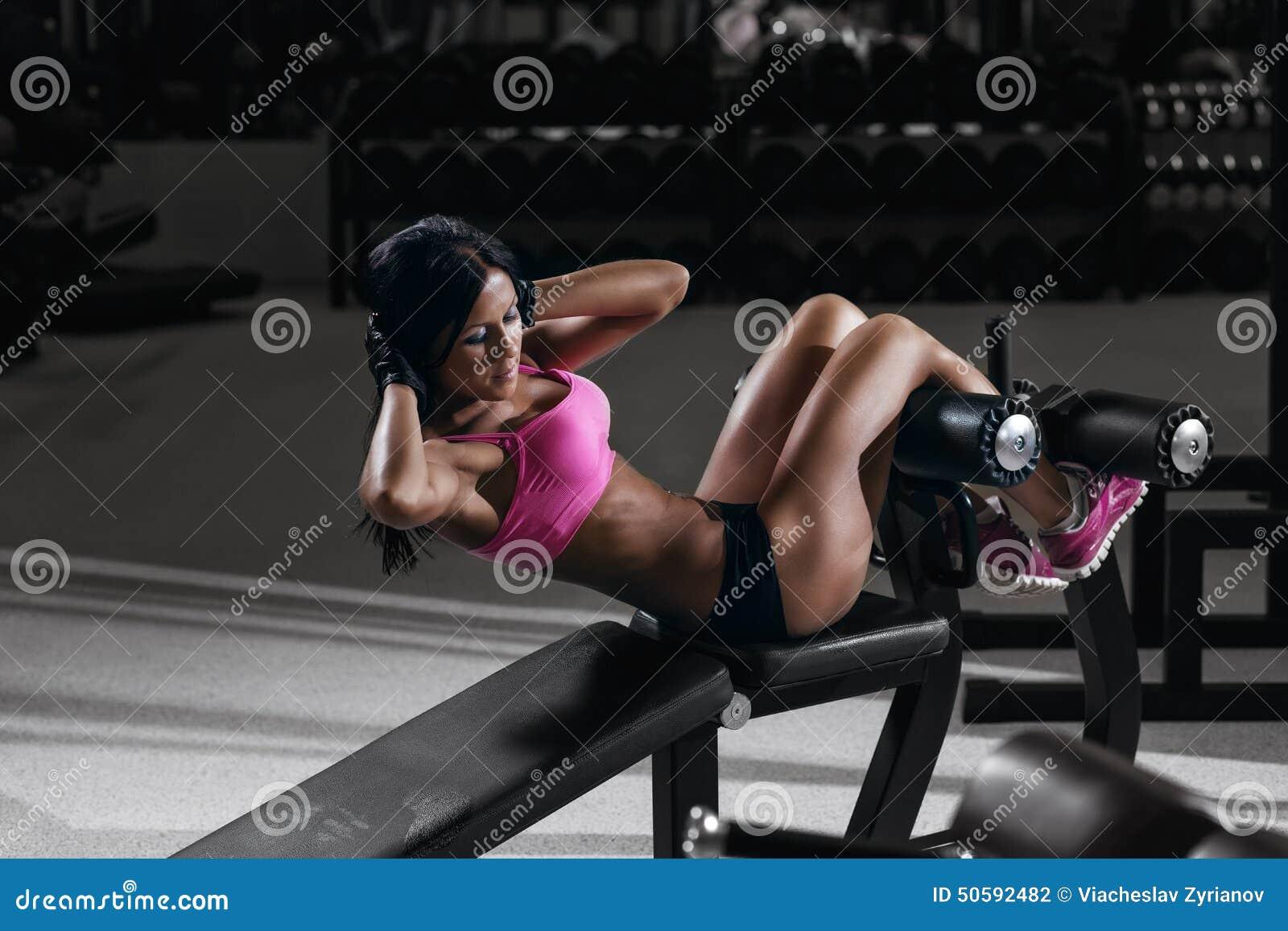 Femme de forme physique dans l usage de sport avec le corps sexy parfait dans le gymnase