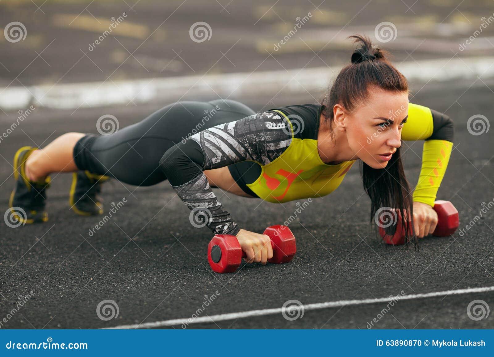 Femme de forme physique faisant des pousées dans le stade, séance d entraînement de formation croisée Formation sportive de fille