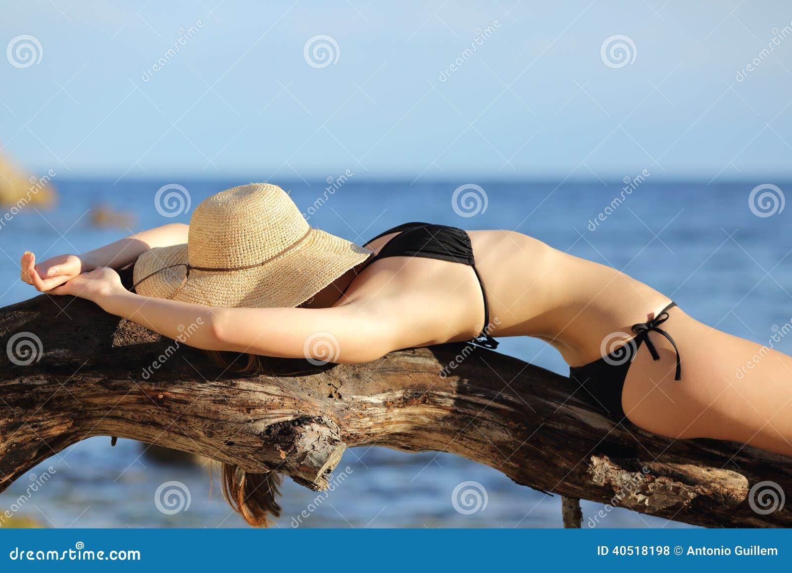 Femme de forme physique prenant un bain de soleil sur le sommeil de plage