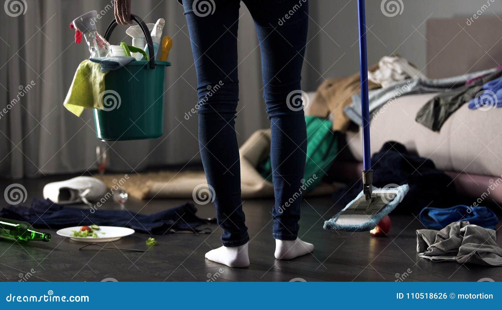 Femme de ménage choquée se tenant dans la chambre d hôtel malpropre avec le balai et le seau de lavage