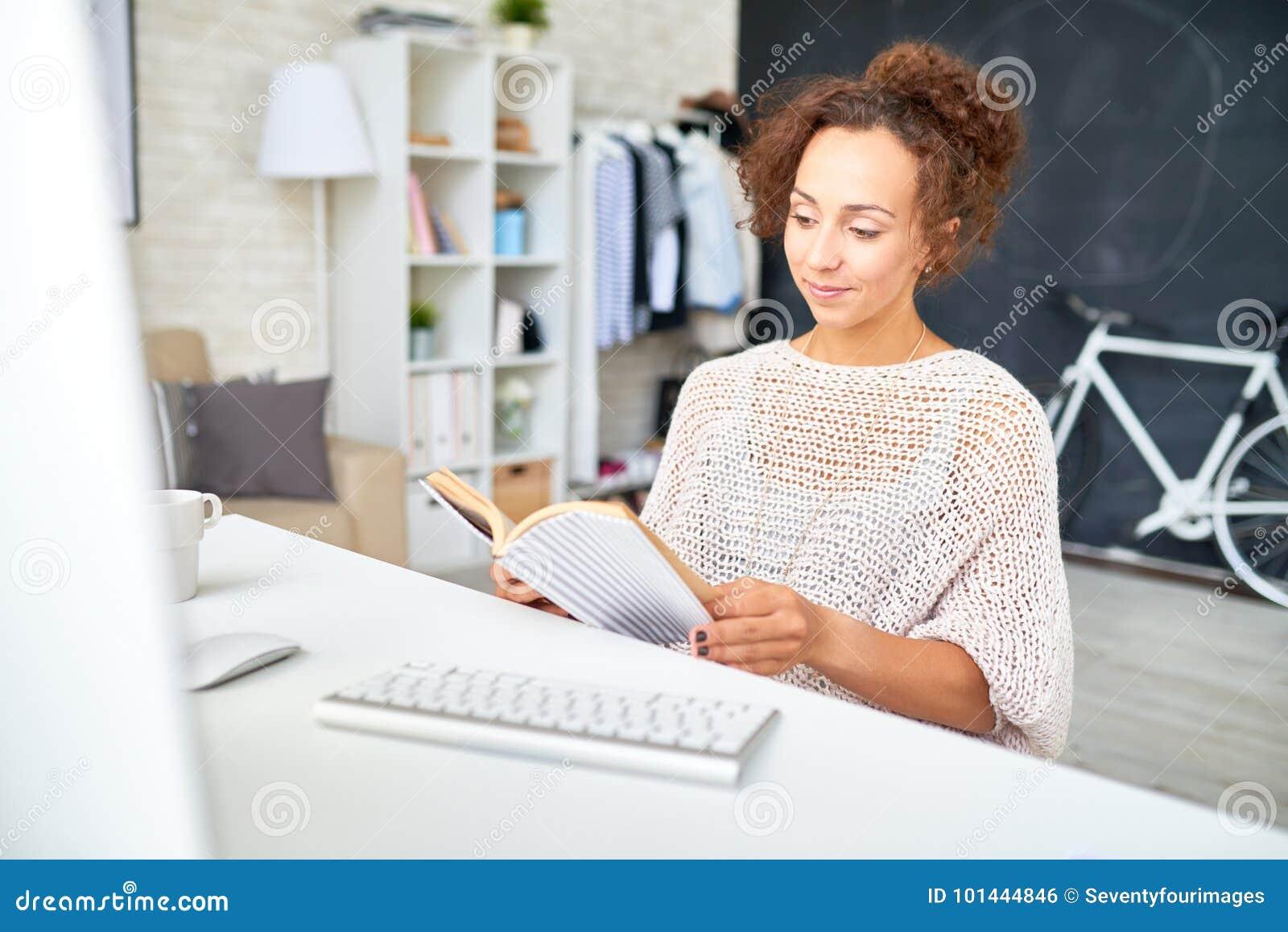Femme de métis détendant au bureau dans le siège social