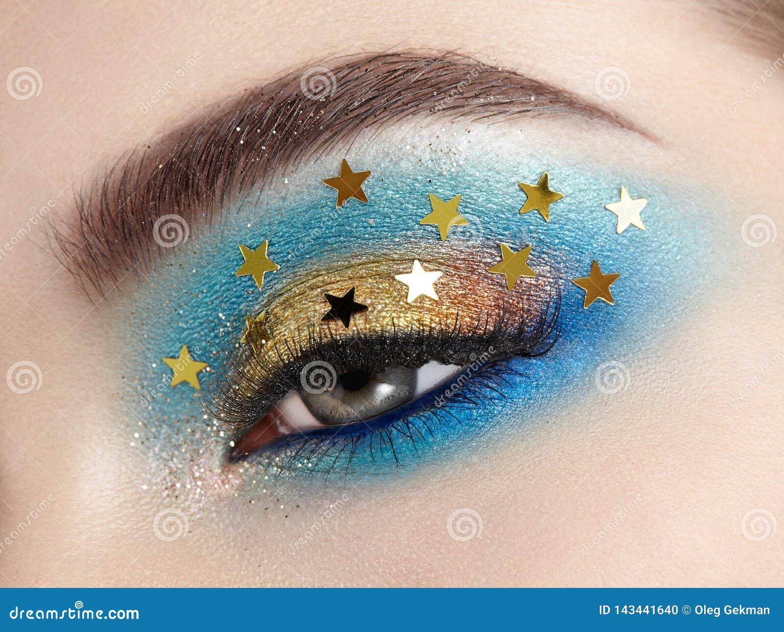 Femme de maquillage d oeil avec les étoiles décoratives