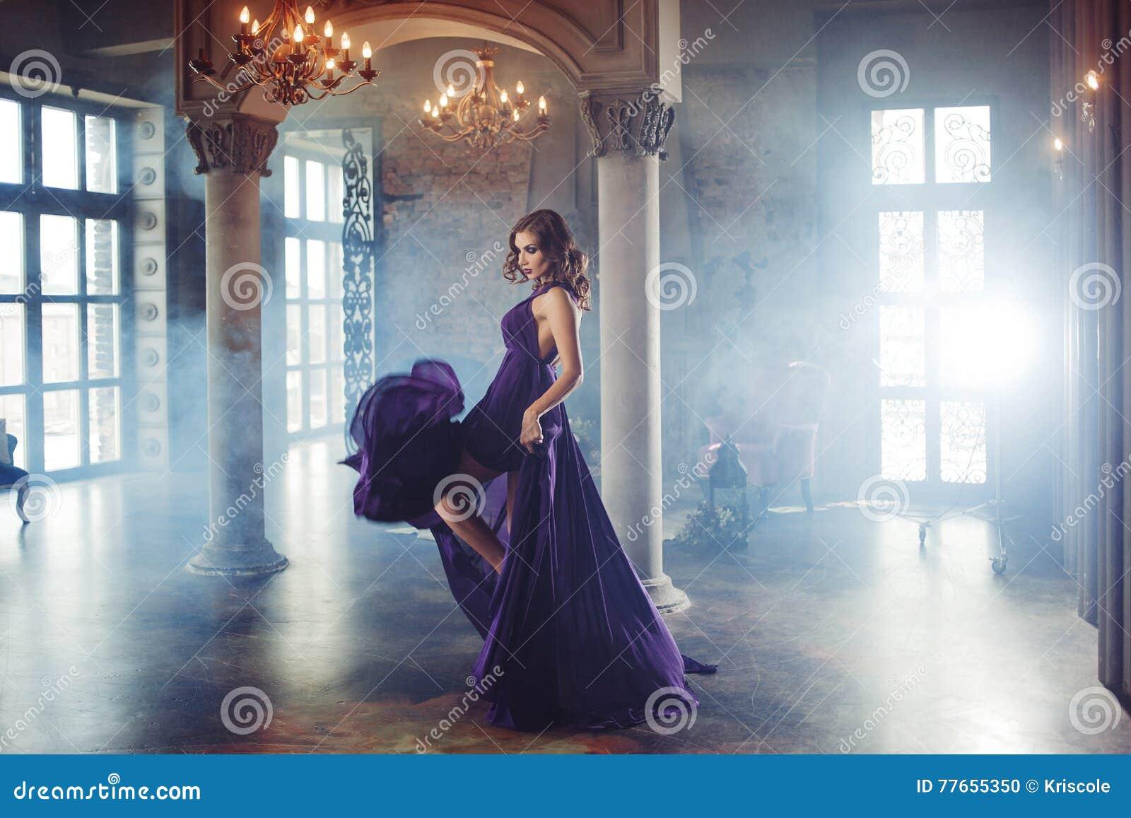 Femme de modèle de brune de beauté en égalisant la robe pourpre Maquillage de luxe et coiffure de belle mode
