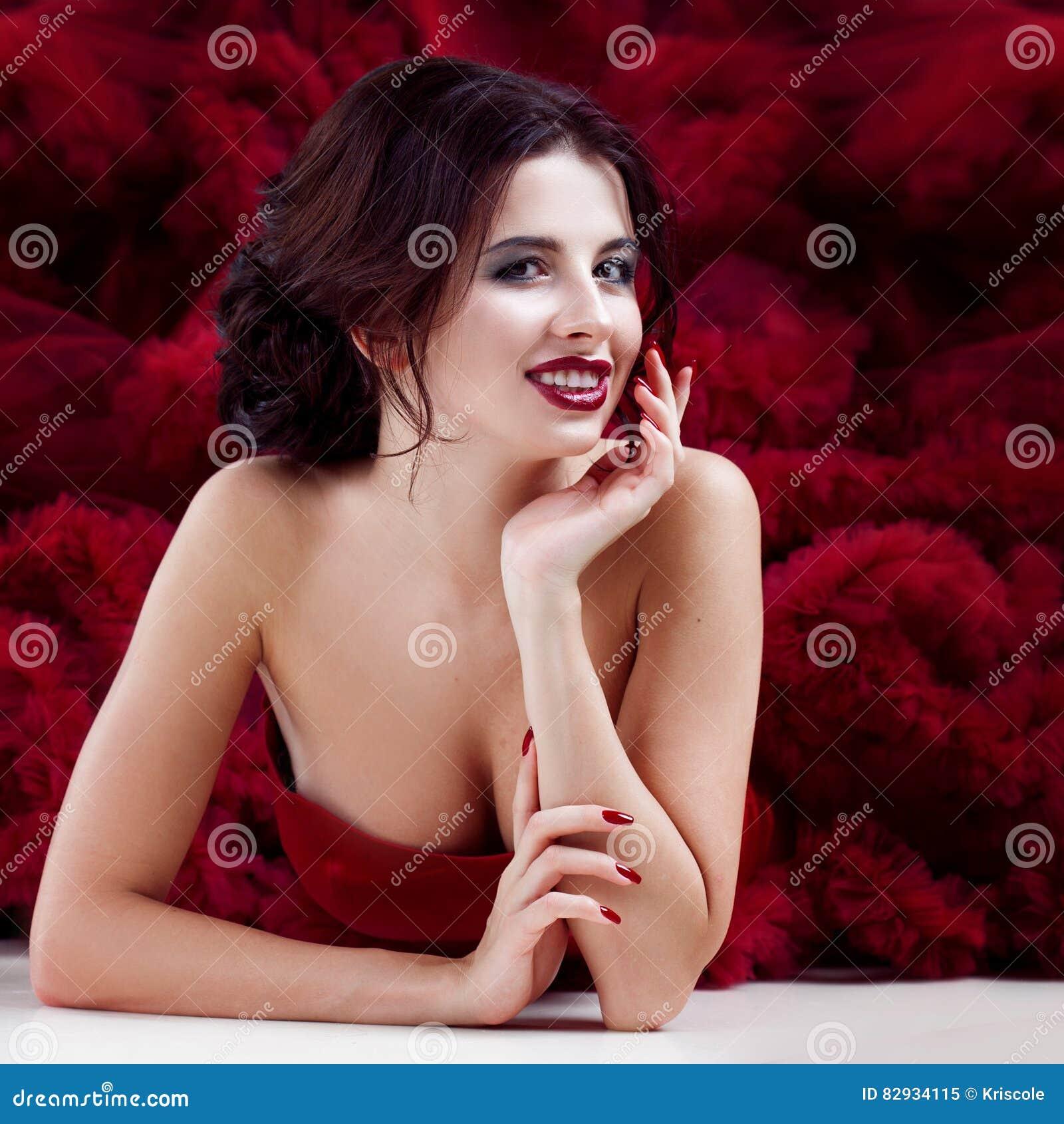 e86e986fa62 Femme de modèle de brune de beauté en égalisant la robe rouge Le maquillage  de luxe et la coiffure de belle mode