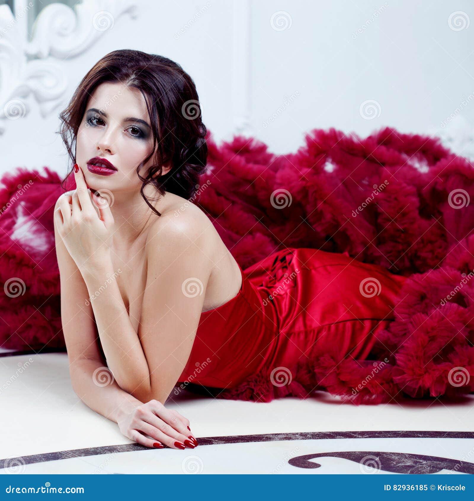 Femme de modèle de brune de beauté en égalisant la robe rouge Maquillage de luxe et coiffure de belle mode