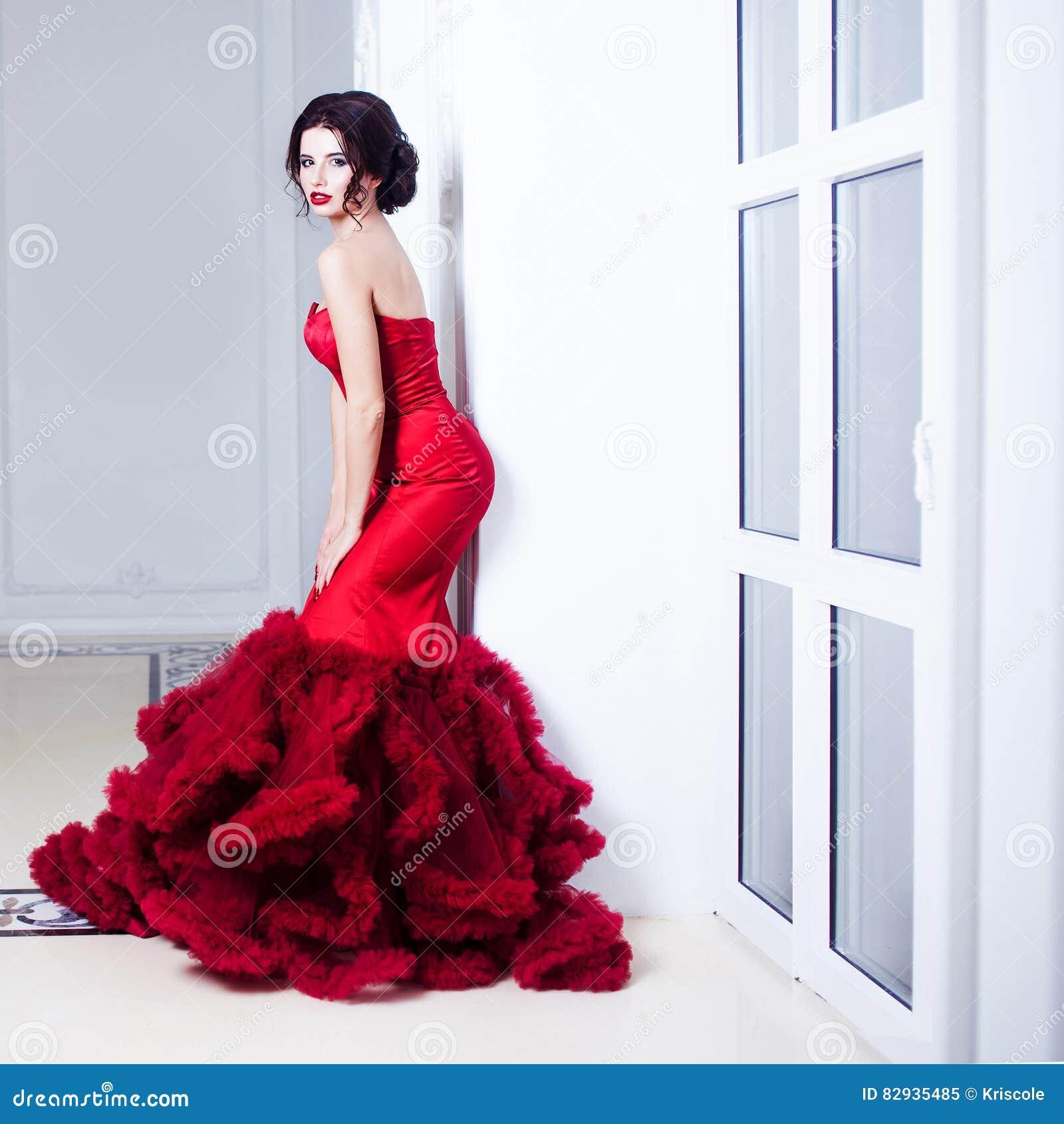 Femme de modèle de brune de beauté en égalisant la robe rouge Maquillage de luxe et coiffure de belle mode Silhouette séduisante