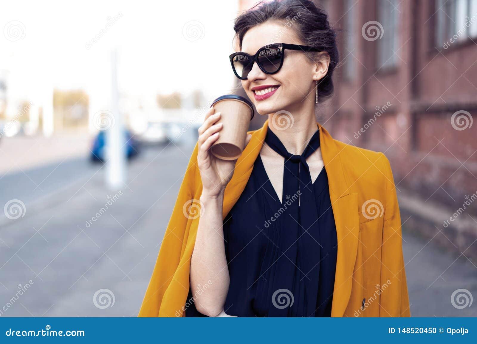 Femme de mode de portrait dans des lunettes de soleil marchant sur la rue Elle utilise la gu?pe, souriant pour d?grossir