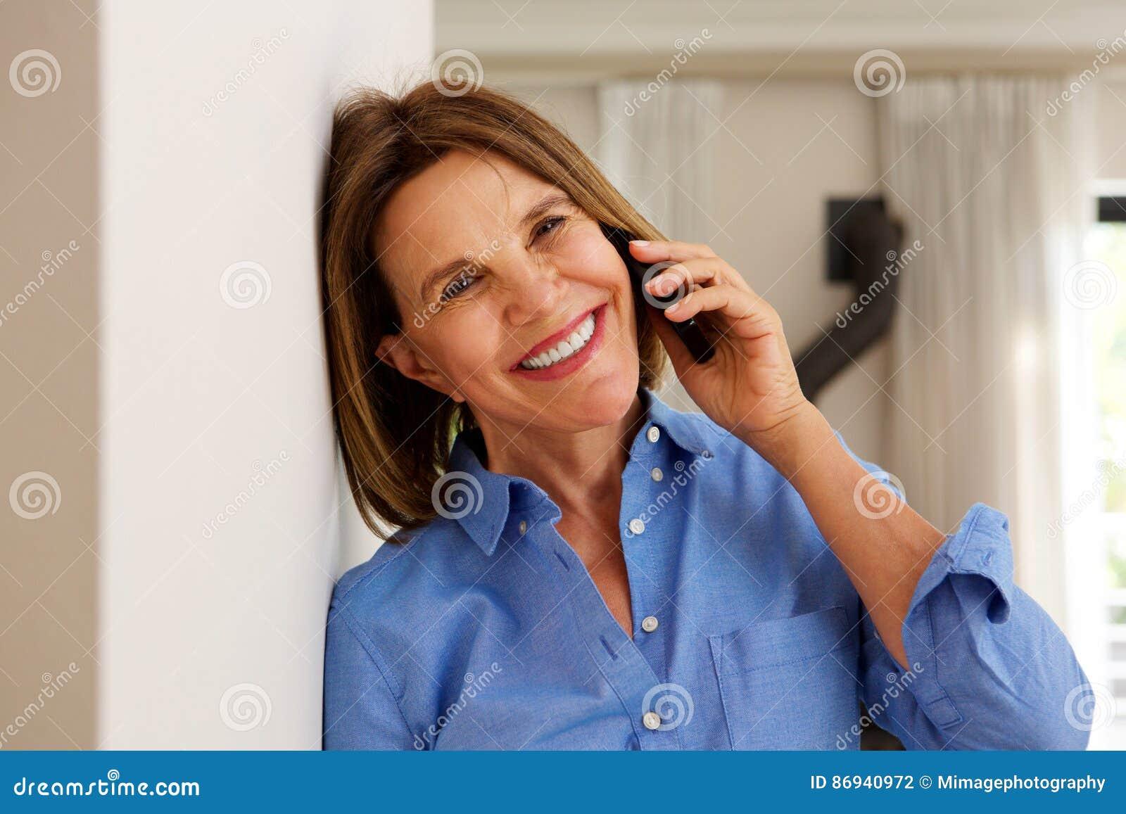 Femme de Moyen Âge se penchant contre le mur et parlant au téléphone portable