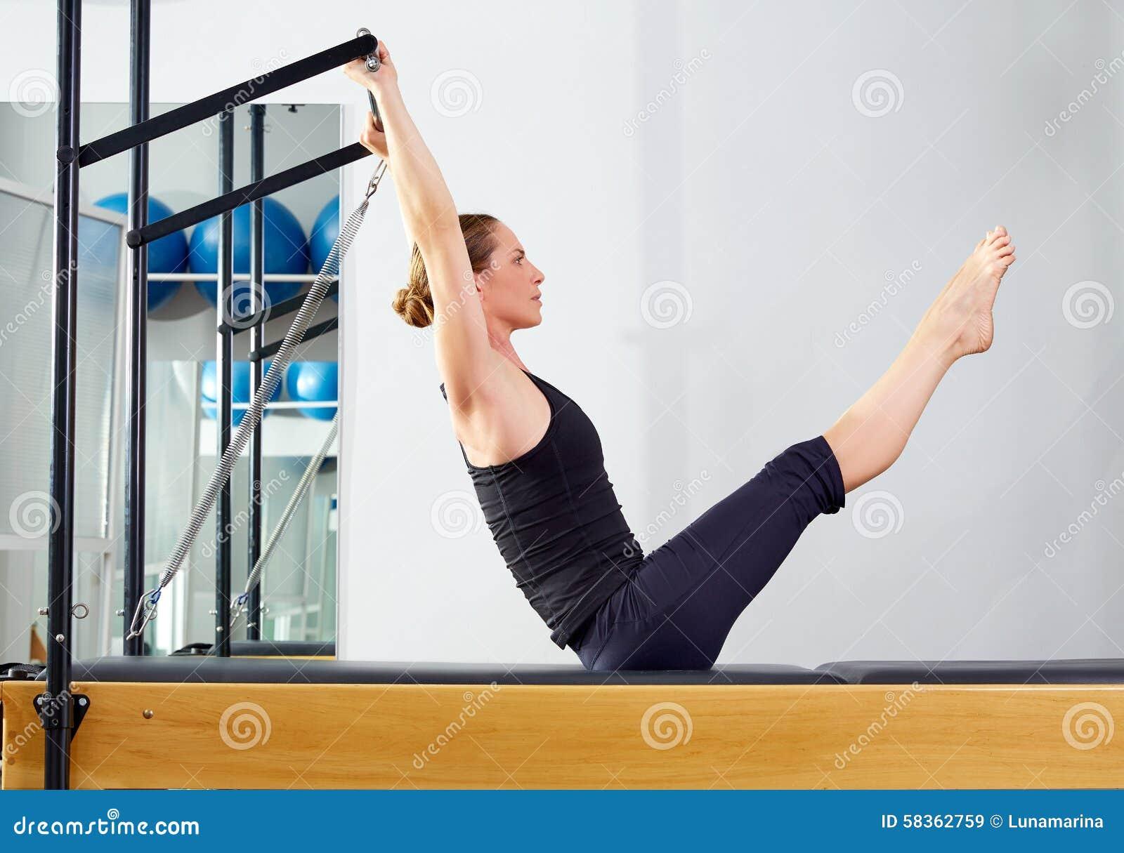 Femme de Pilates dans l exercice d énigme de réformateur au gymnase