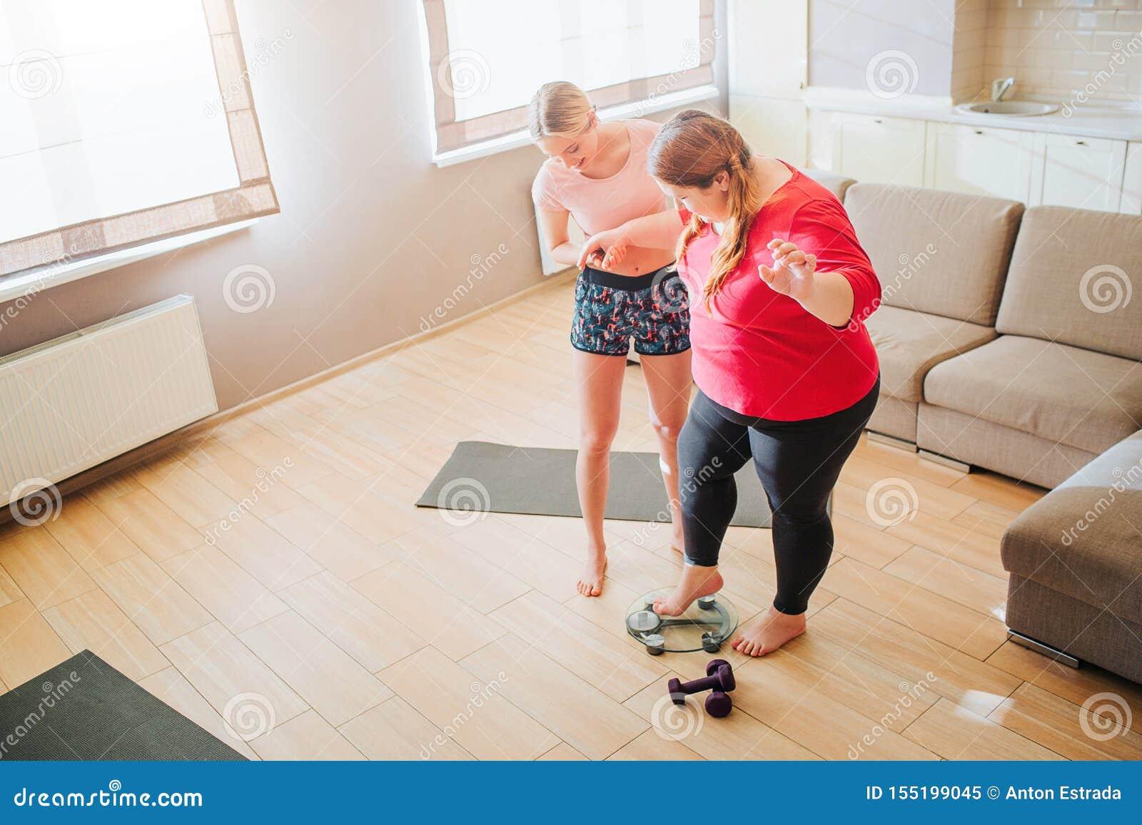Femme de poids excessif de jeune aide mince de modèle à tenir sur l échelle de poids dans le salon Halt?res sur le plancher Mod?l