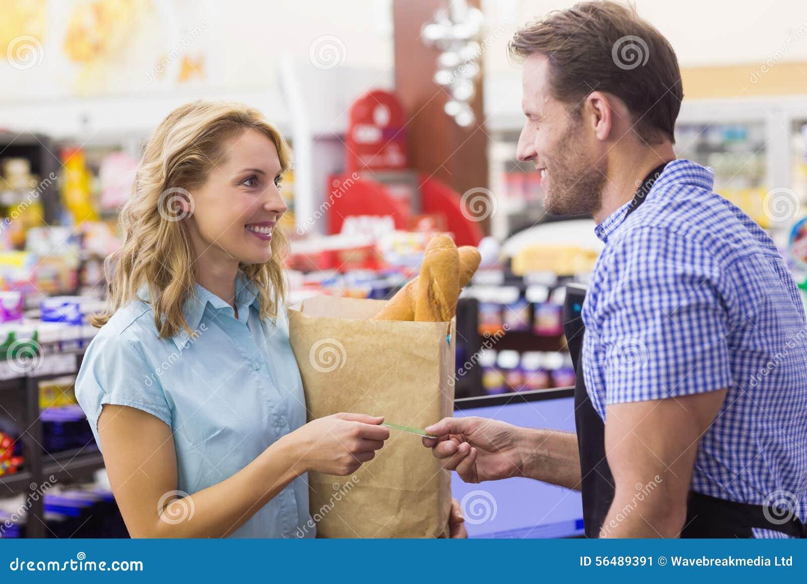 Femme de Smilingm à la caisse enregistreuse payant avec la carte de crédit