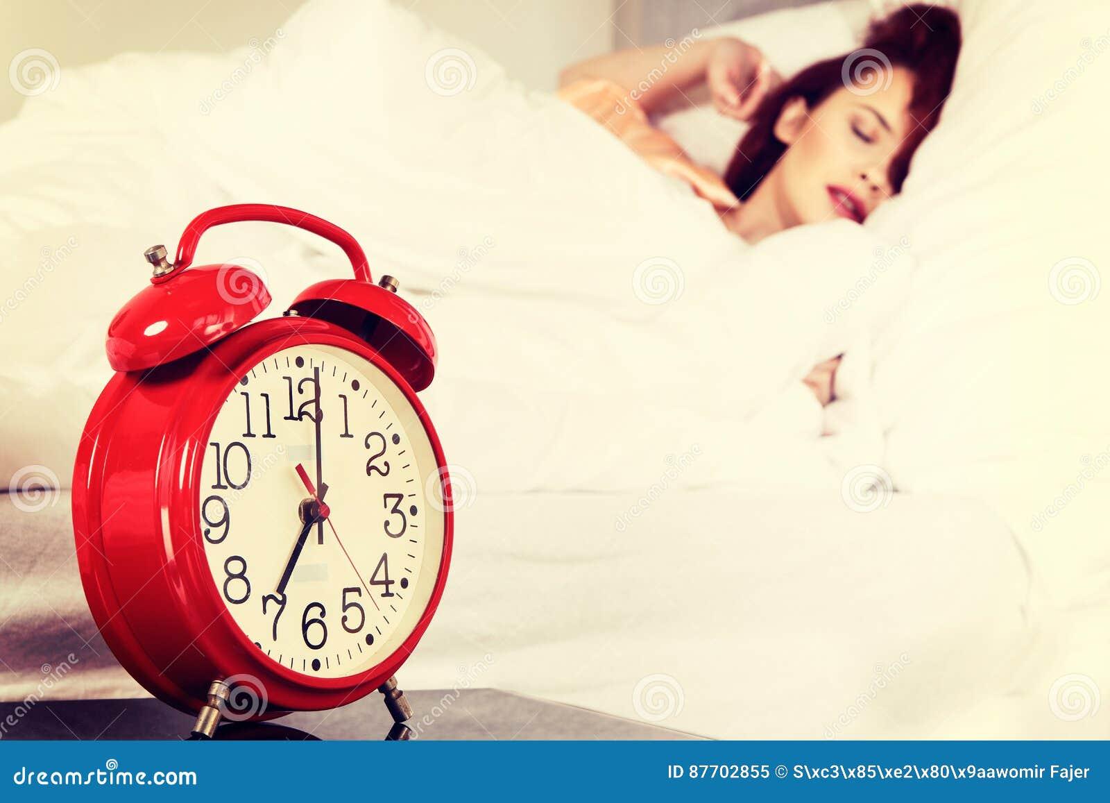Femme de sommeil avec son réveil émouvant de main sur le lit