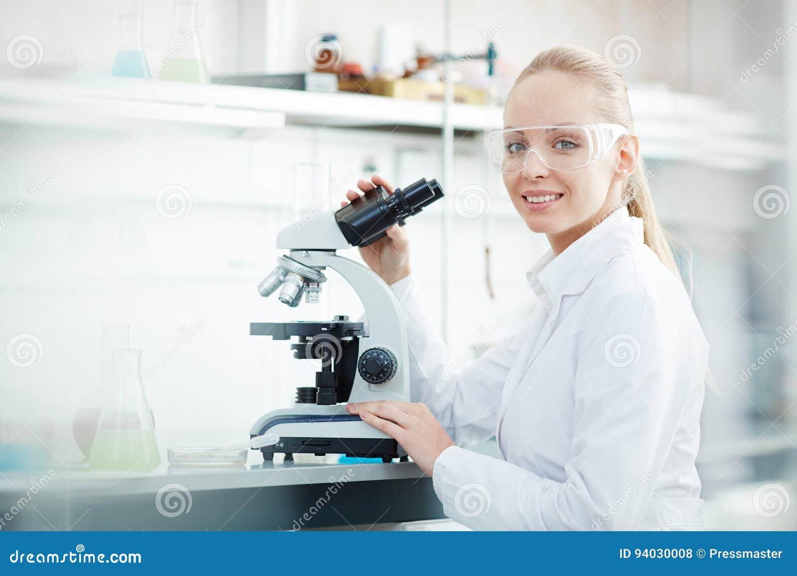 Femme de sourire à l aide du microscope dans le laboratoire