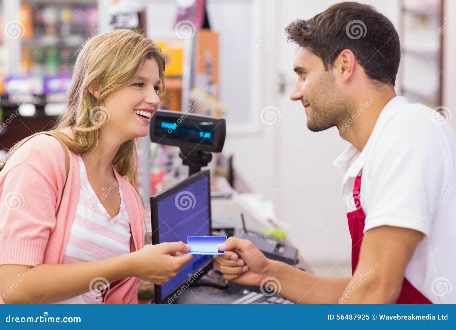 Femme de sourire à la caisse enregistreuse payant avec la carte de crédit