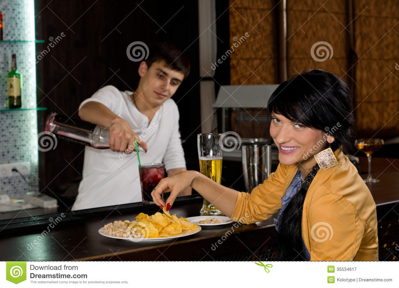 Femme de sourire amicale s asseyant à une barre