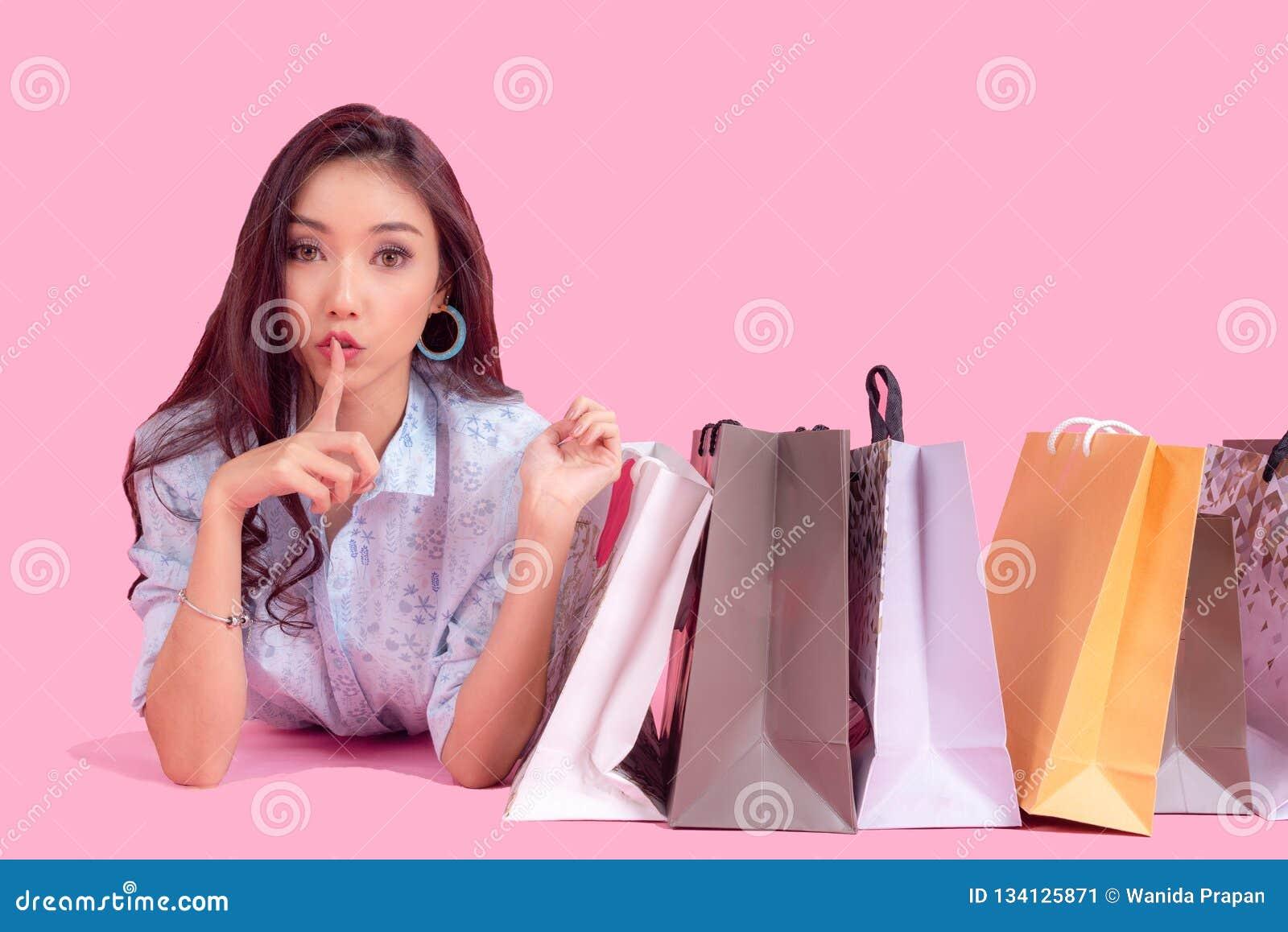 Femme de sourire asiatique si heureuse avec ses achats dans les vêtements décontractés avec des sacs à provisions sur le fond de