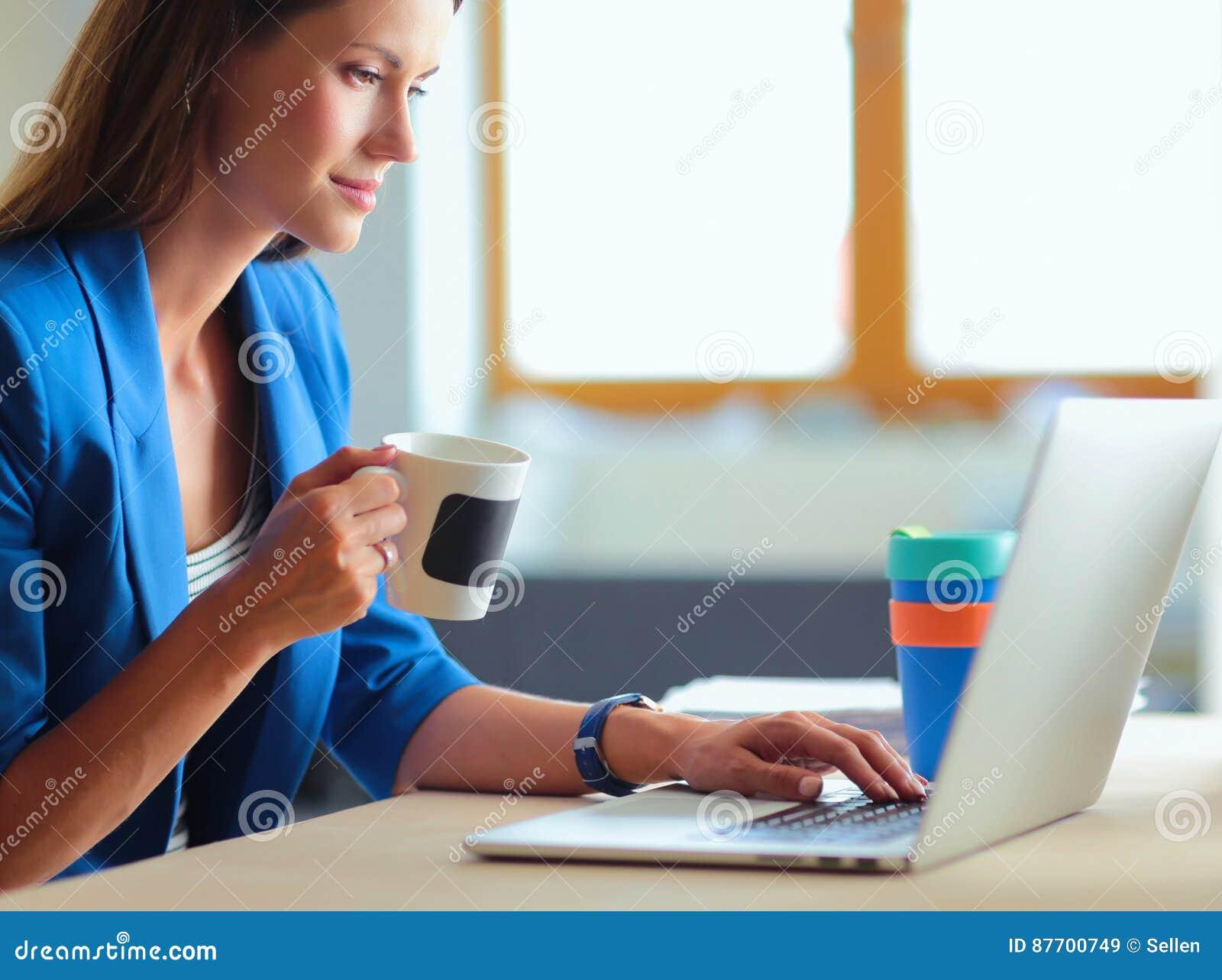 Femme de sourire attirante d affaires s asseyant au bureau, tenant une tasse de café