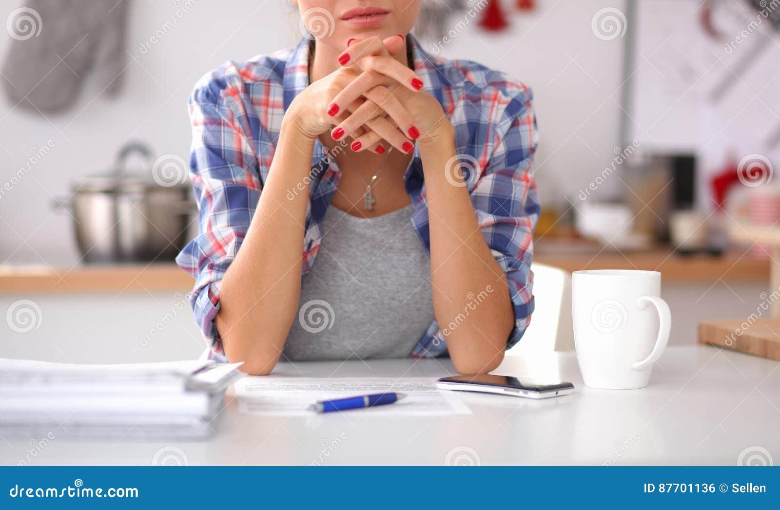 Femme de sourire avec la tasse du café et du journal dans la cuisine