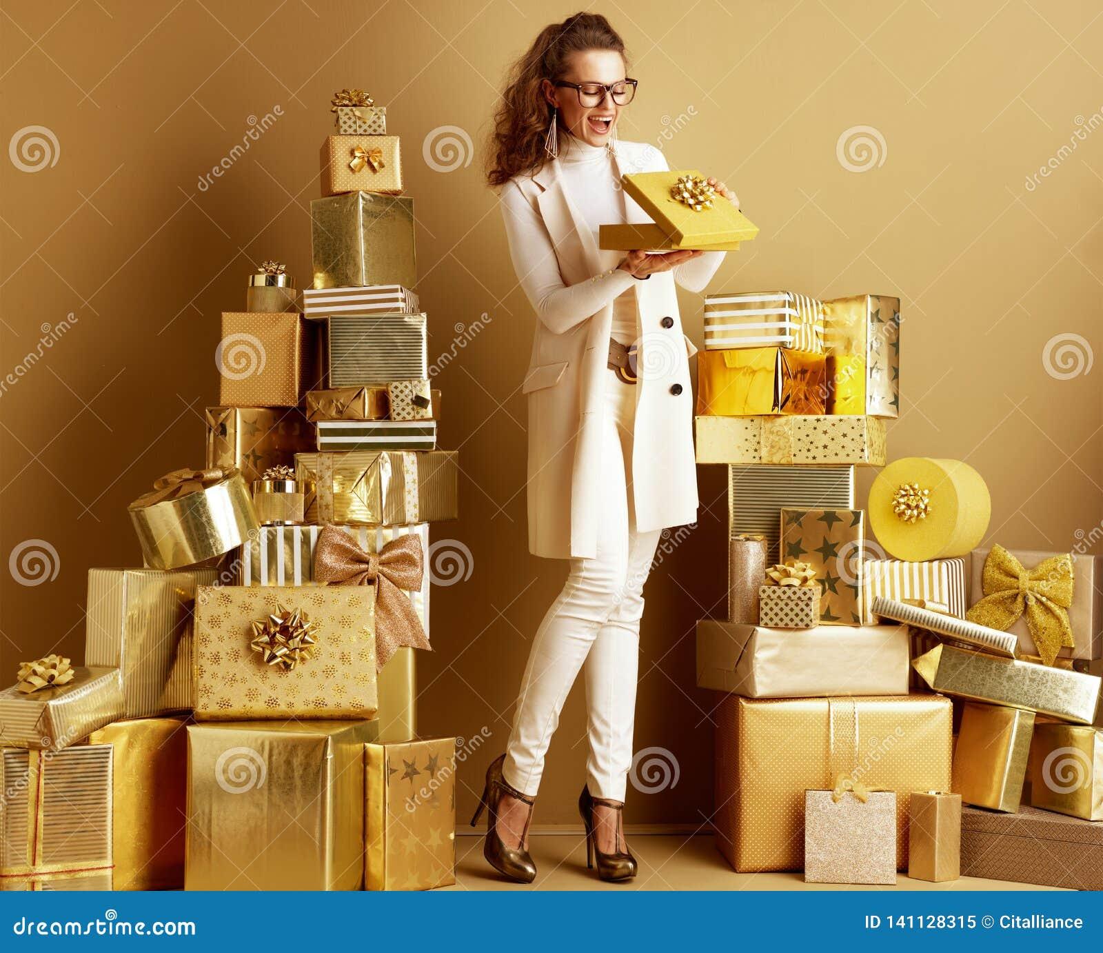 Femme de sourire de client ouvrant la boîte actuelle d or avec l arc