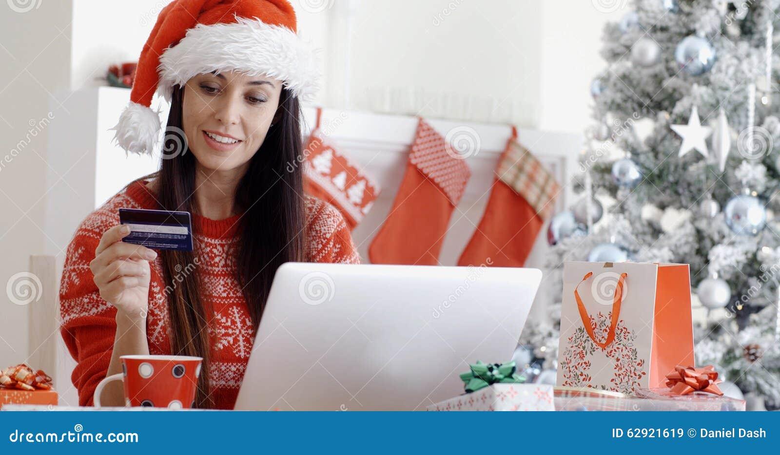 Femme de sourire faisant des achats en ligne de Noël