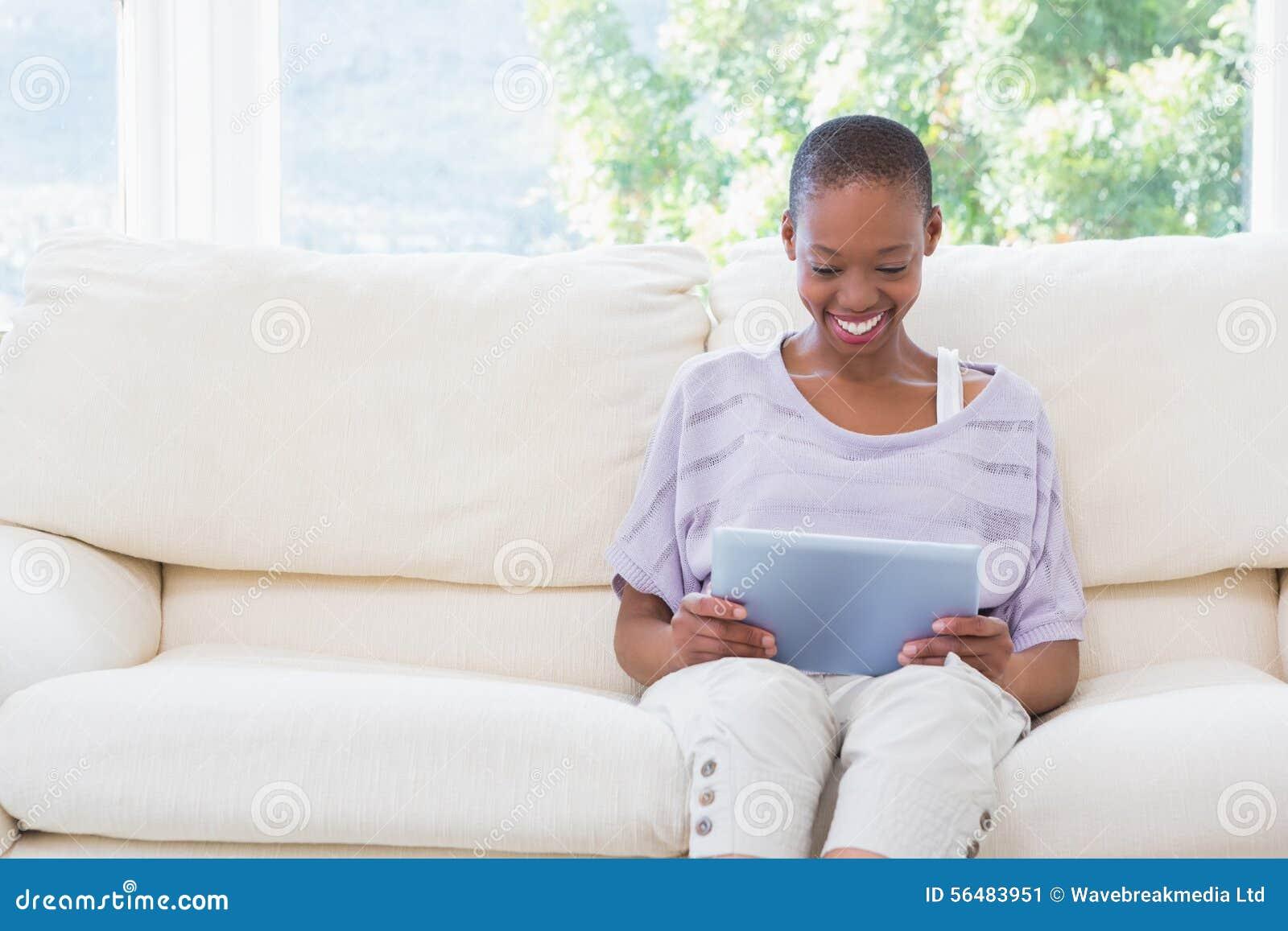 Femme de sourire heureuse à l aide du comprimé numérique sur le divan