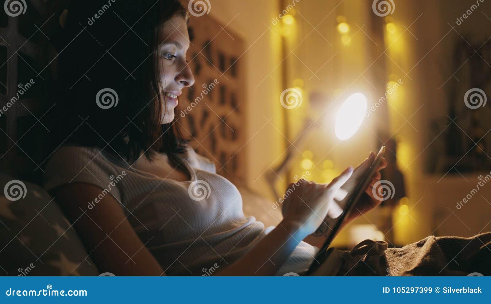 Femme de sourire heureuse à l aide de la tablette pour partager le media social se trouvant dans le lit à la maison la nuit