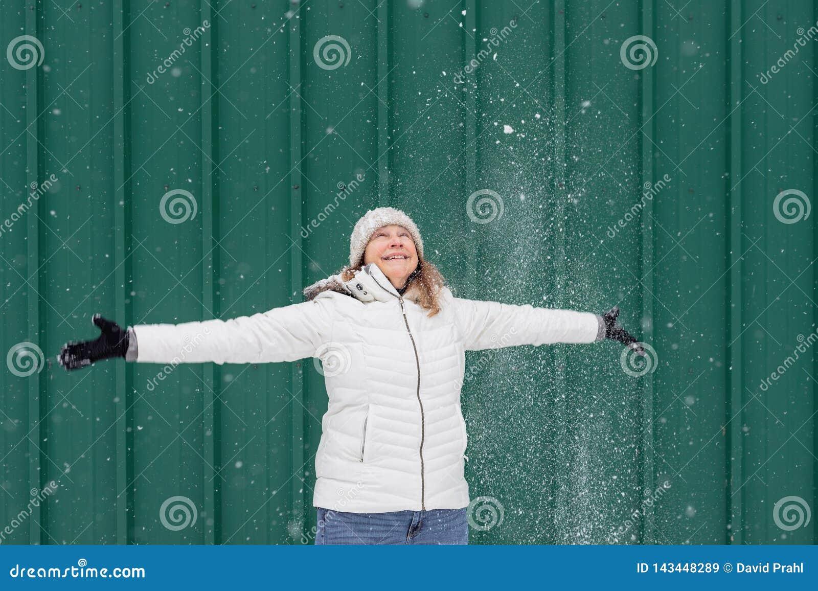 Femme de sourire jouant dans l extérieur frais de neige