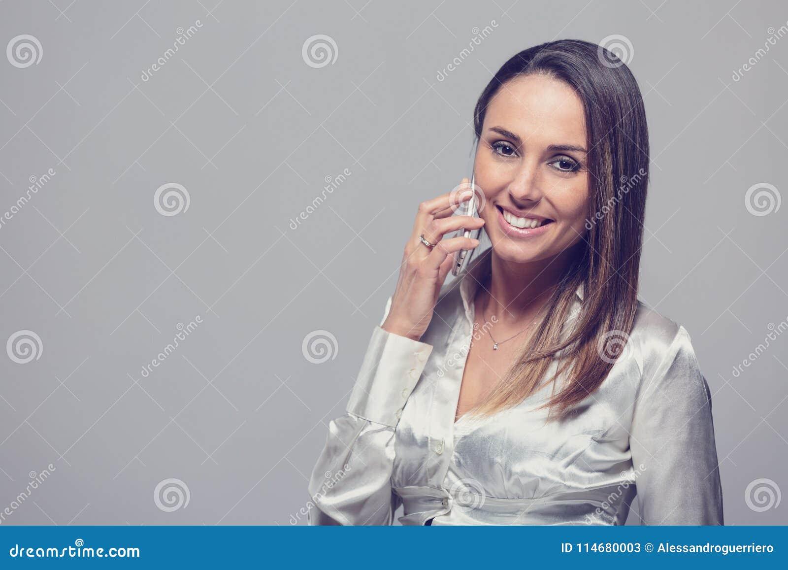 Femme de sourire parlant sur le smartphone