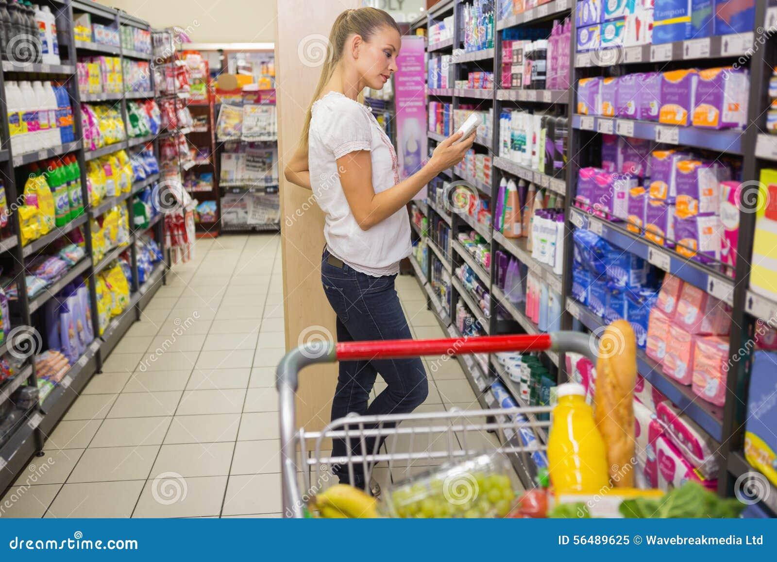Femme de sourire prenant la lotion dans l étagère du bas-côté