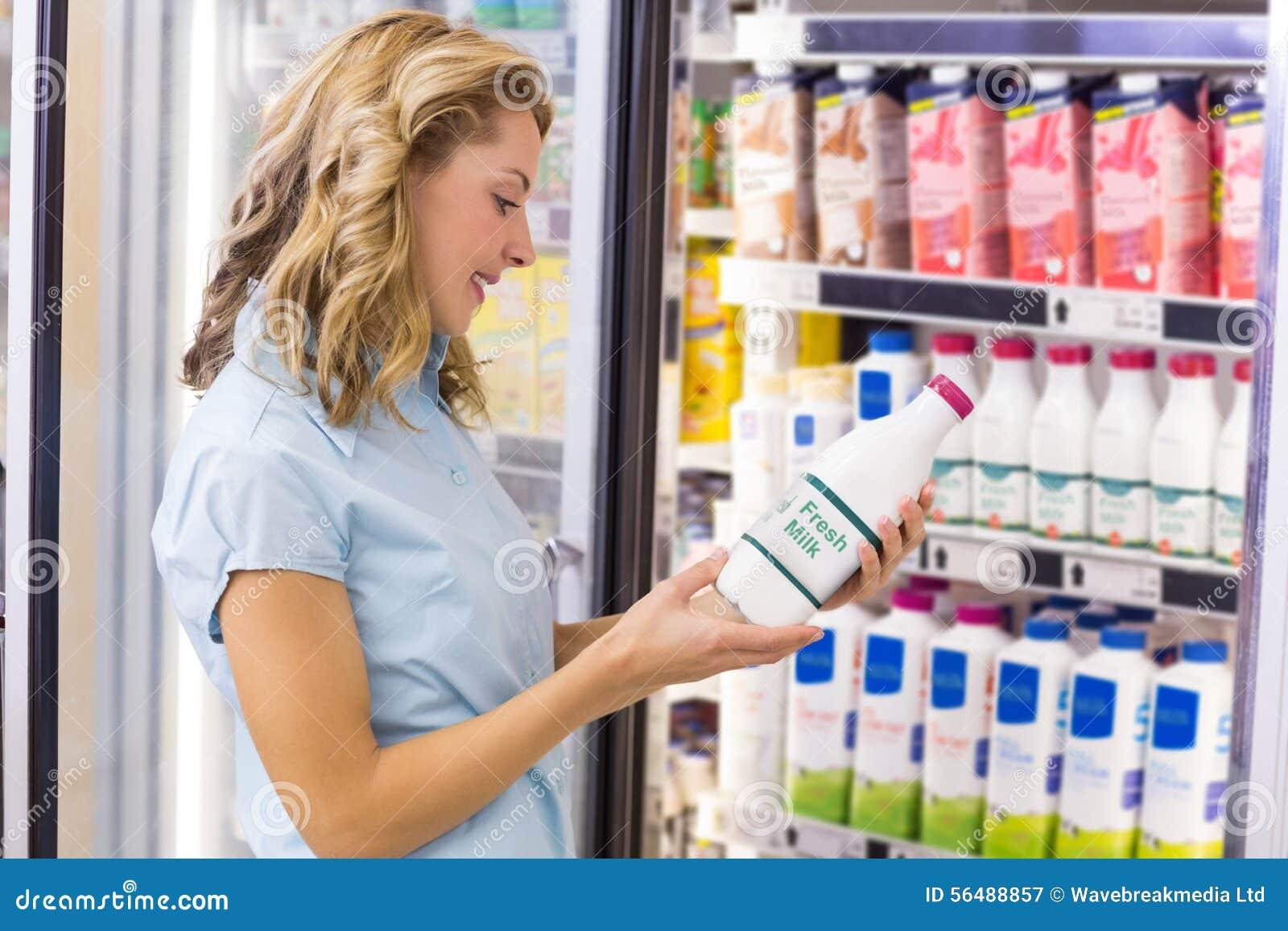 Femme de sourire regardant une bouteille à lait