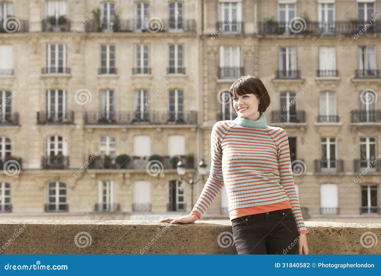 Femme de sourire sur le pont contre des Chambres de ville