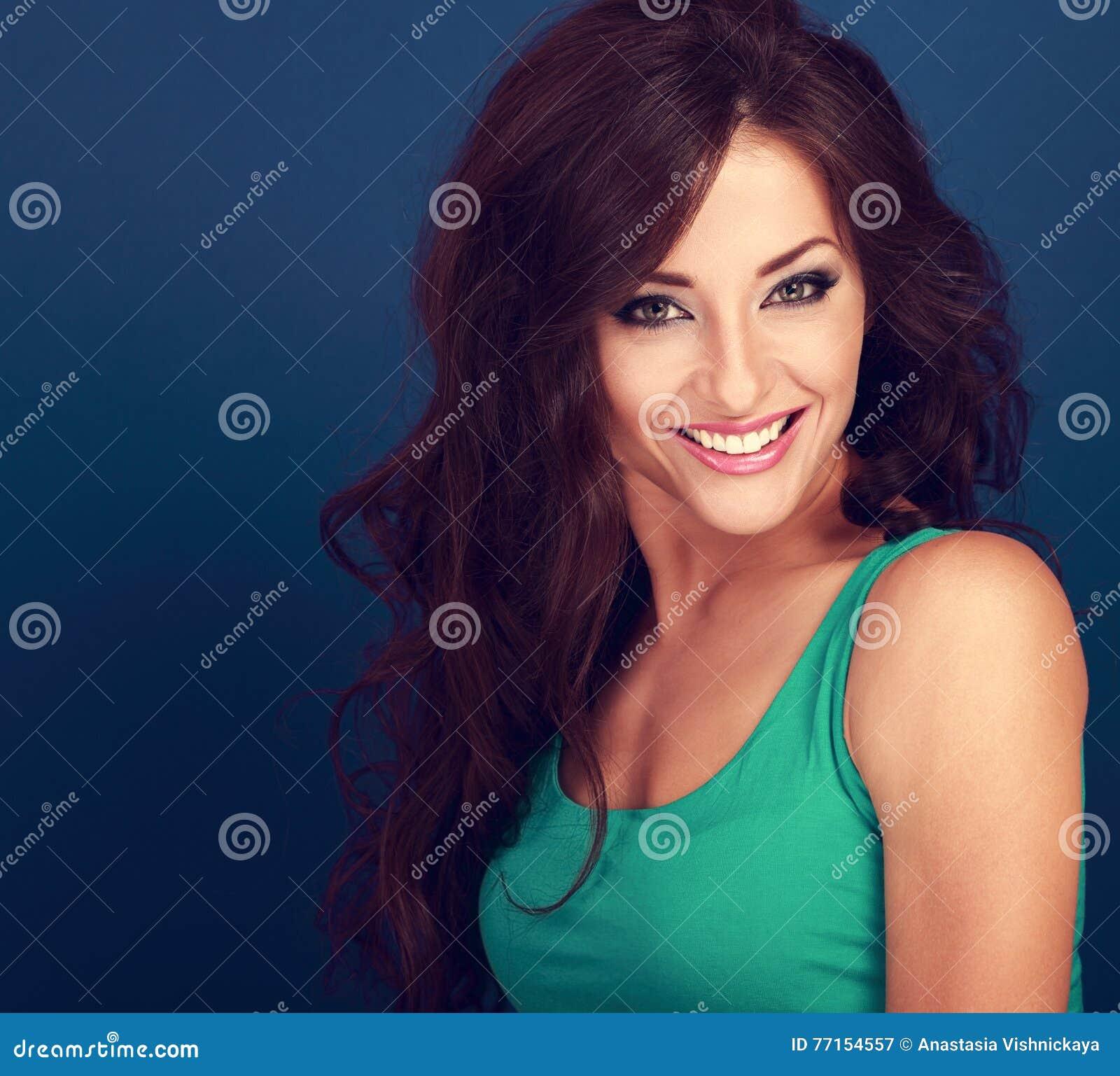 Femme de sourire toothy heureuse avec de longs cheveux bruns bouclés regardant dessus