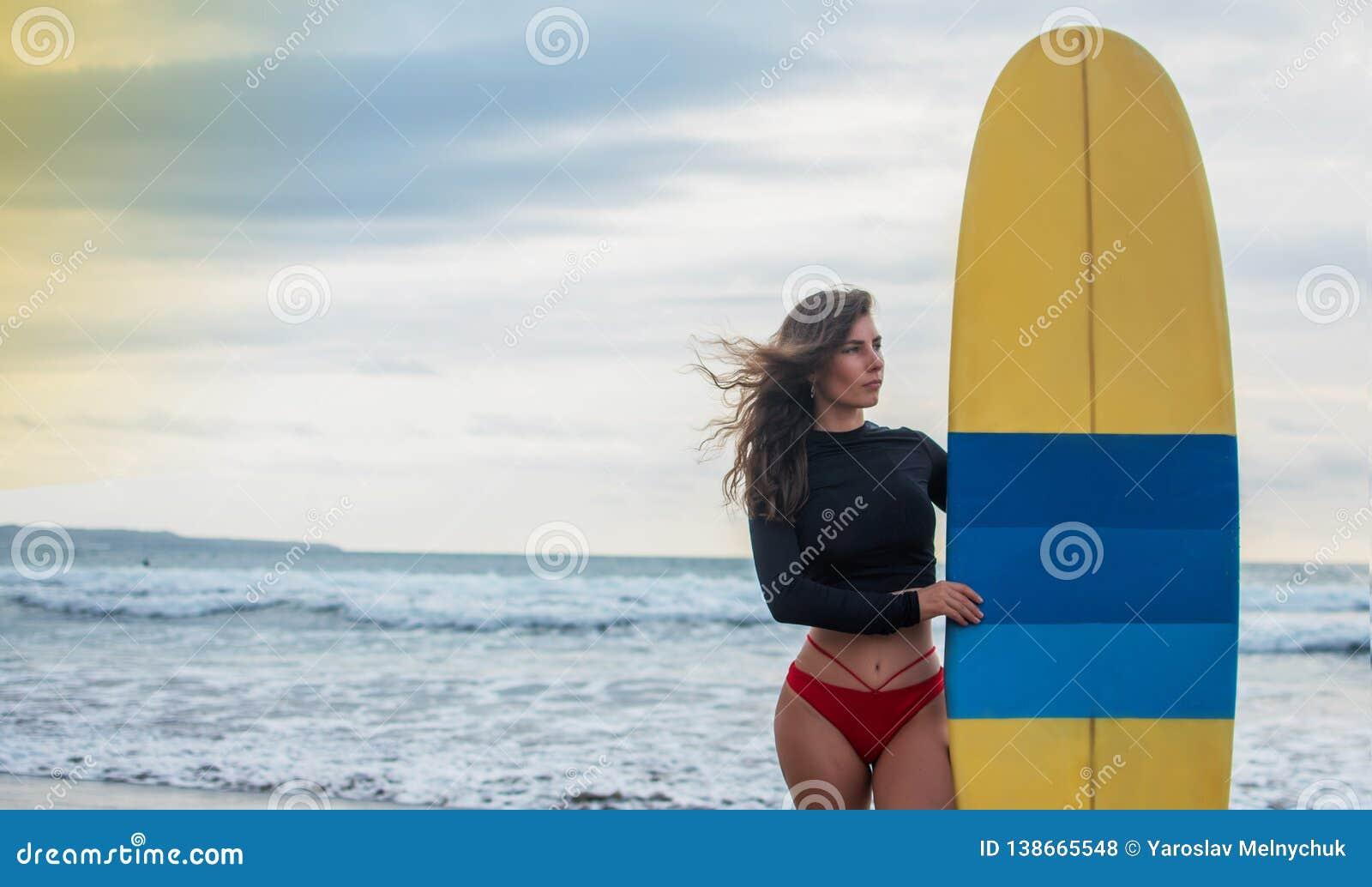 Femme de surfer allant surfant la position avec la planche de surf bleu-jaune sur la plage de Waikiki Fille féminine de bikini ma