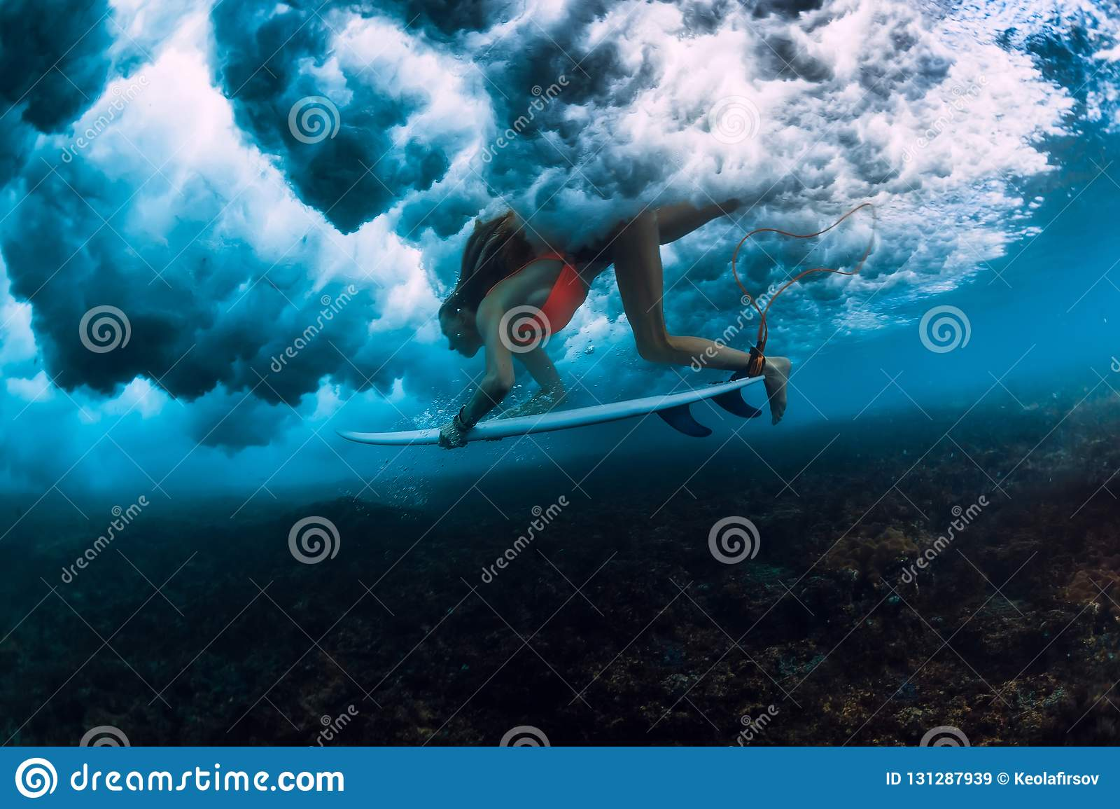 Femme de surfer avec le piqué de panneau de ressac sous l eau avec la vague se brisante dessous grande