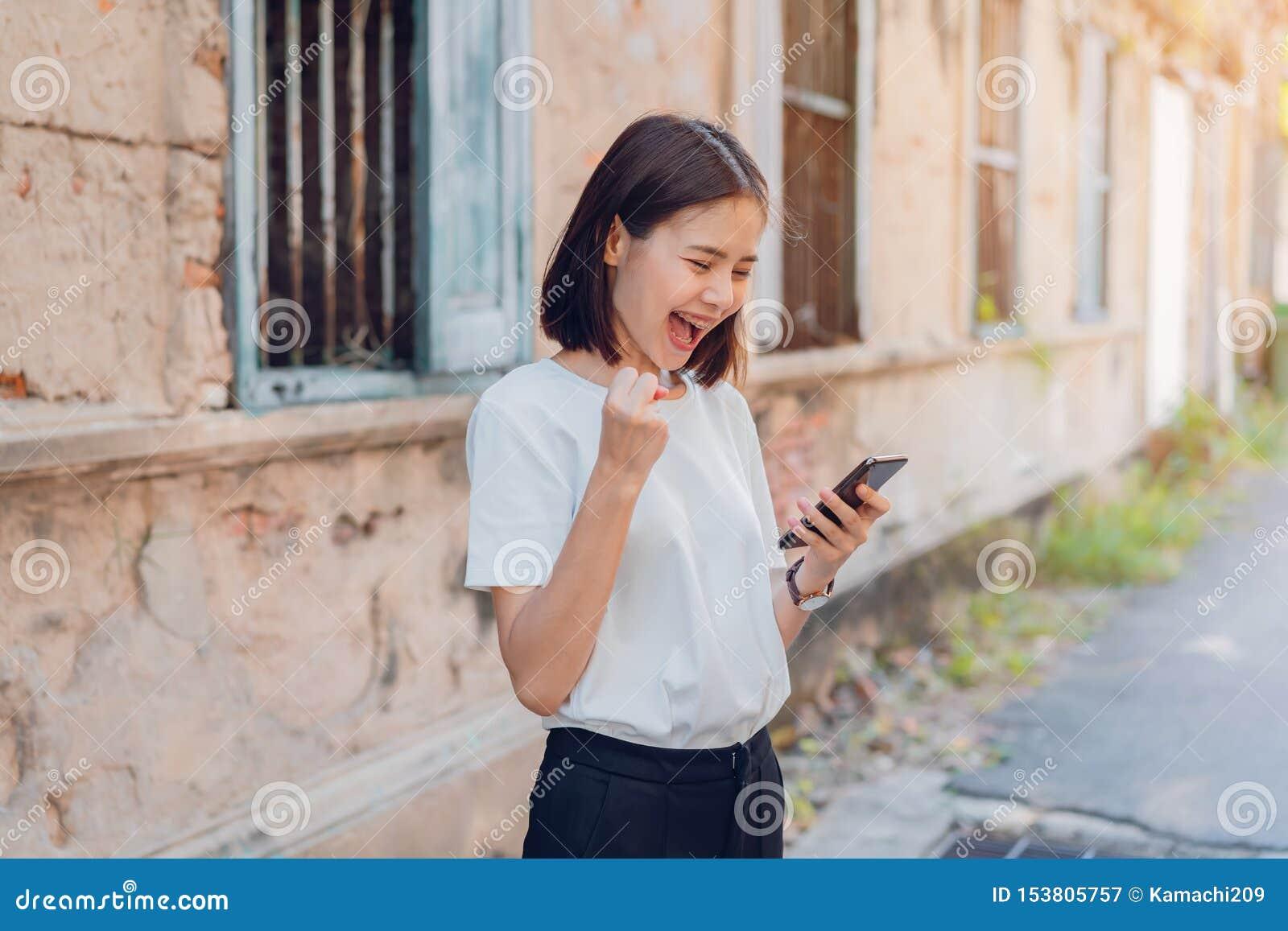 Femme de téléphone intelligent de sourire et se tenant heureux avec stupéfait pour le succès