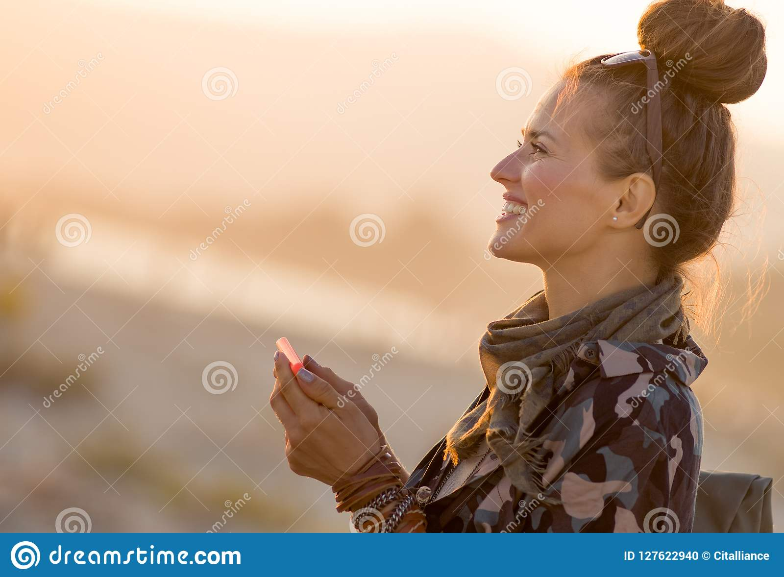 Femme de touristes convenable de sourire avec le smartphone utilisant l APP