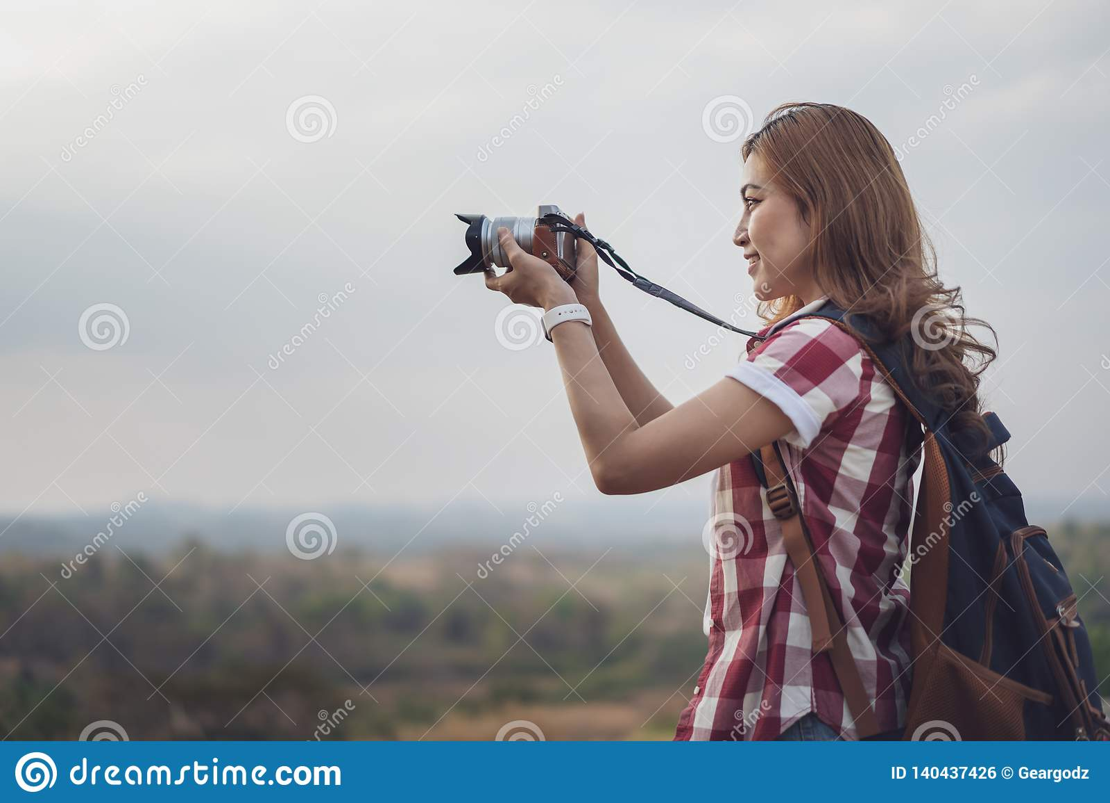 Femme de touristes prenant la photo avec sa caméra en nature