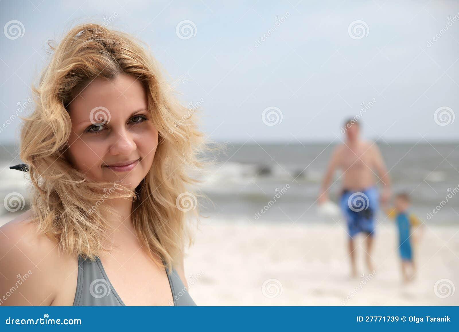 Femme de verticale en fonction sur la plage et le famille de t derrière elle