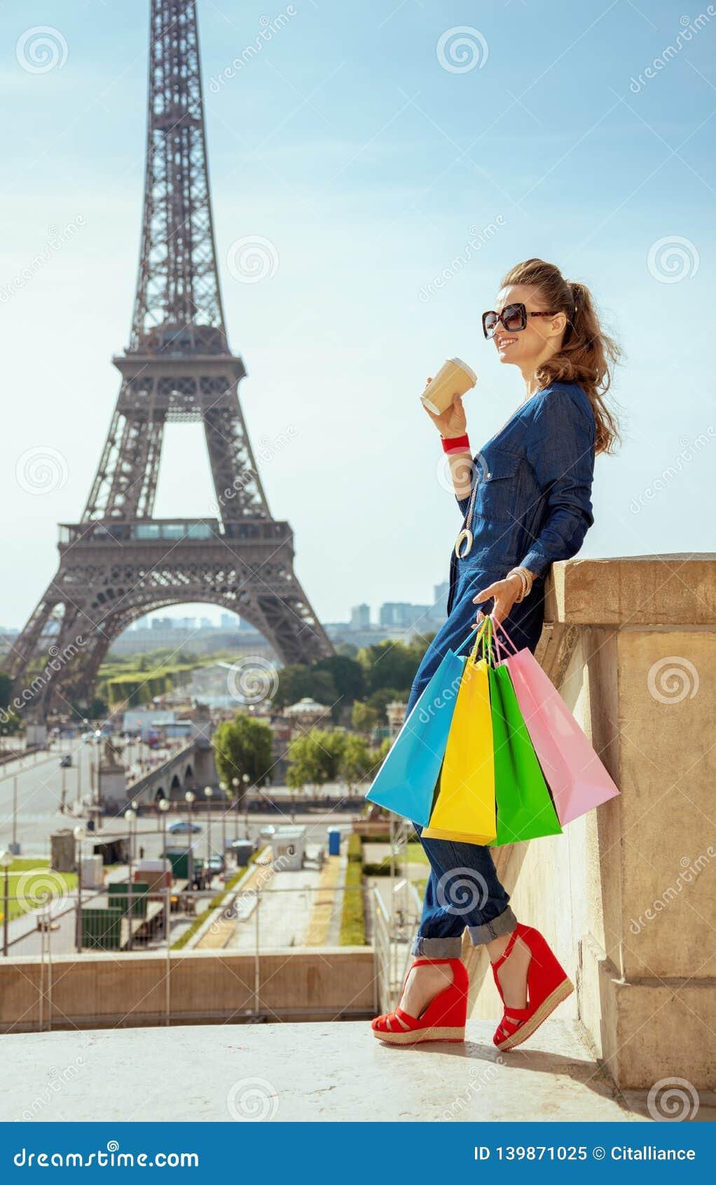 Femme de voyageur avec des sacs à provisions et tasse de café examinant t