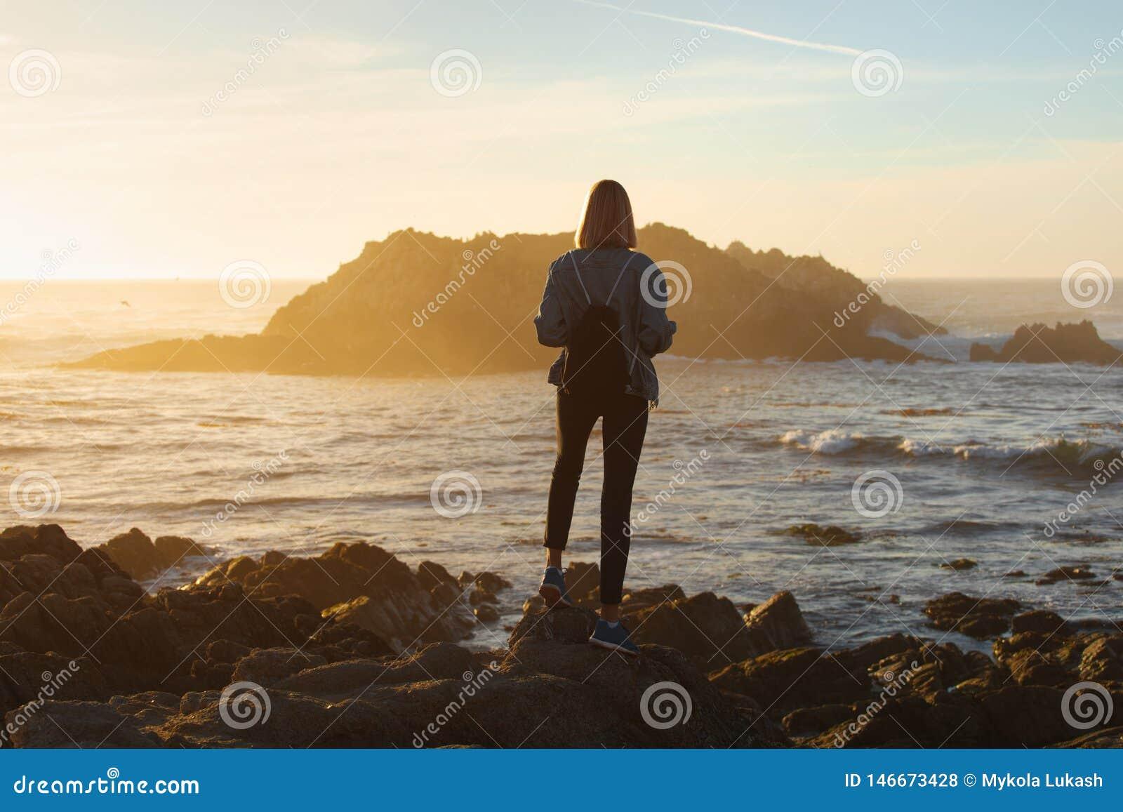 Femme de voyageur avec le sac à dos appréciant la vue d océan, randonneur de fille au coucher du soleil, concept de voyage, la Ca