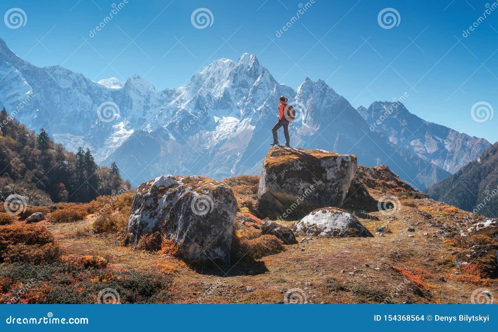 Femme debout avec le sac à dos sur la pierre et la belle montagne