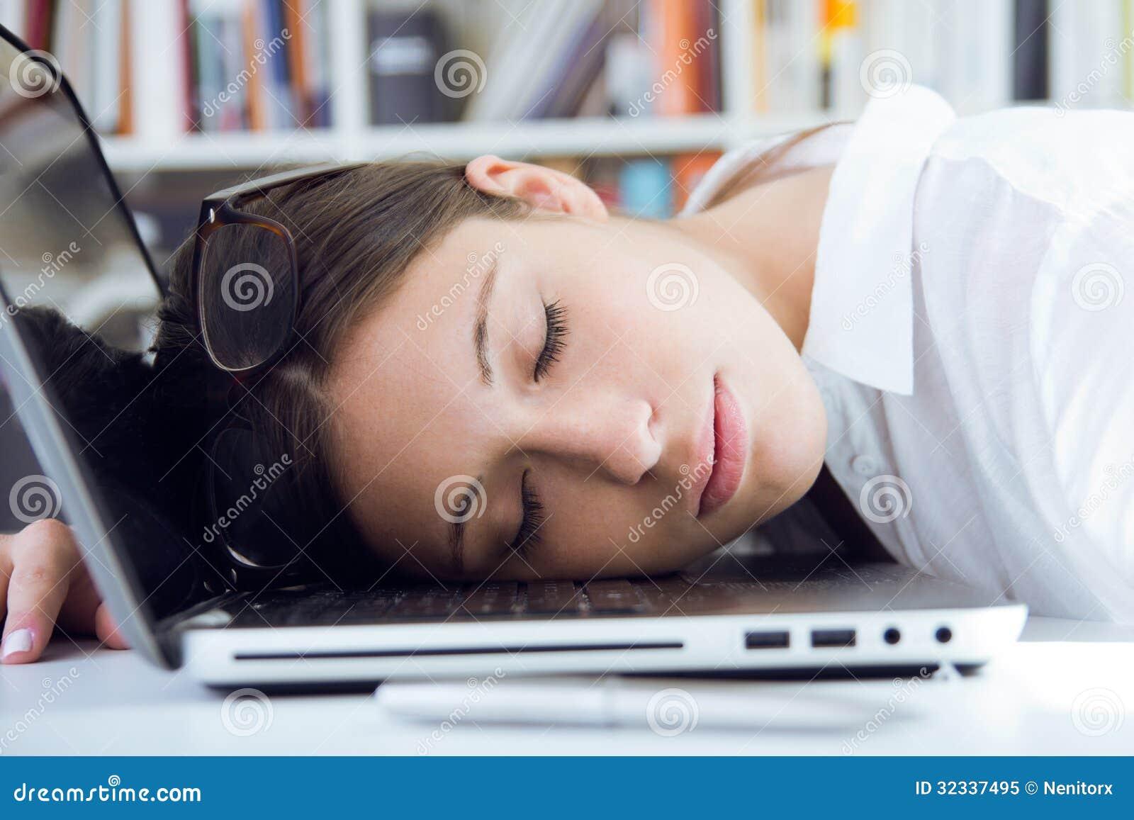 Femme dormant sur son ordinateur portable dans le lieu de travail